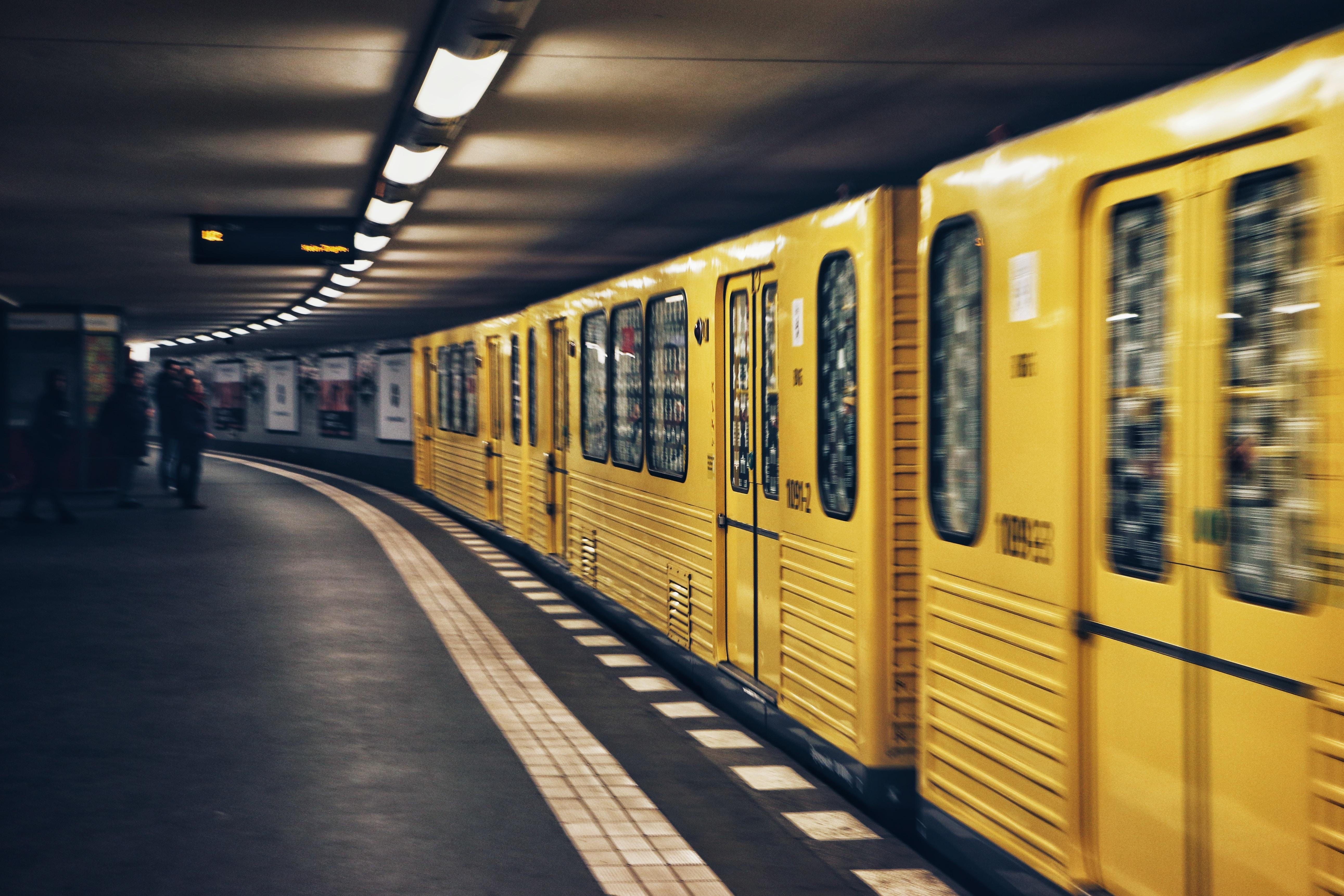 Yellow train cars speed past the platform