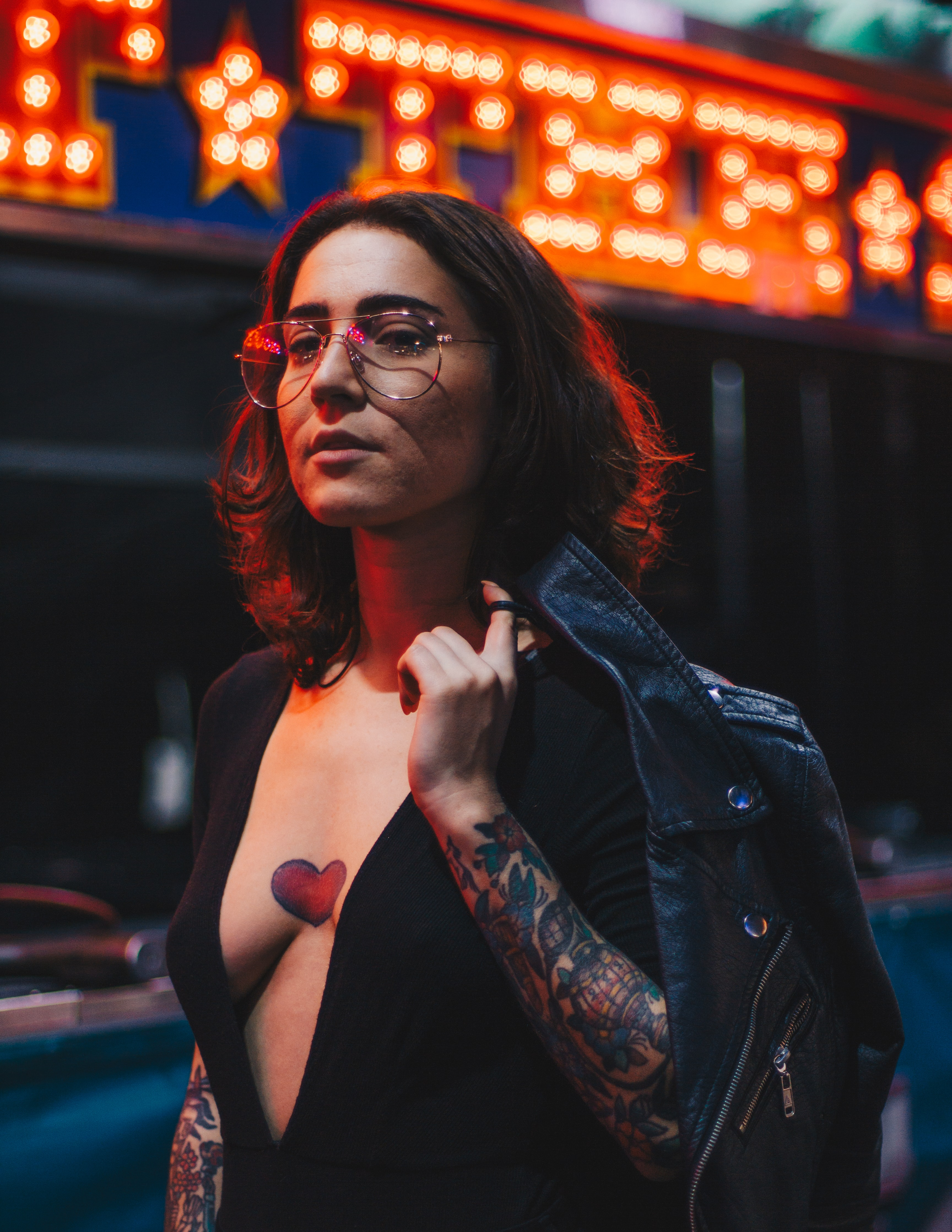 A tattooed woman in glasses with a heart inked on her exposed chest