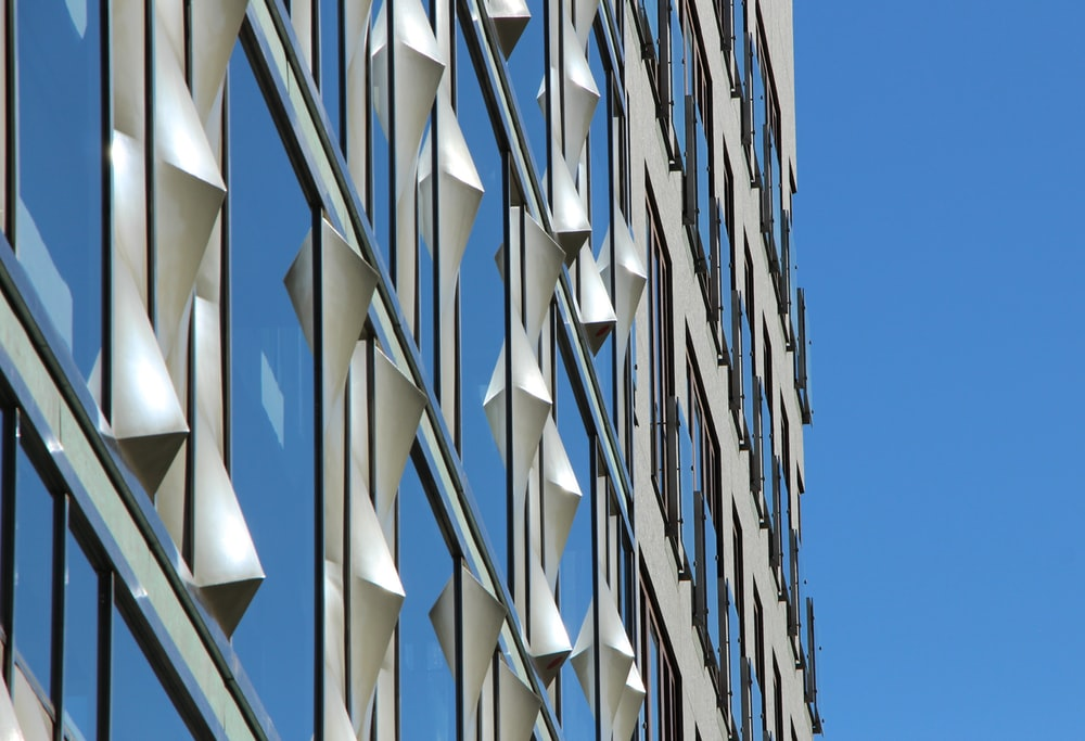low-angle photography of curtain wall building under blue sky at daytime