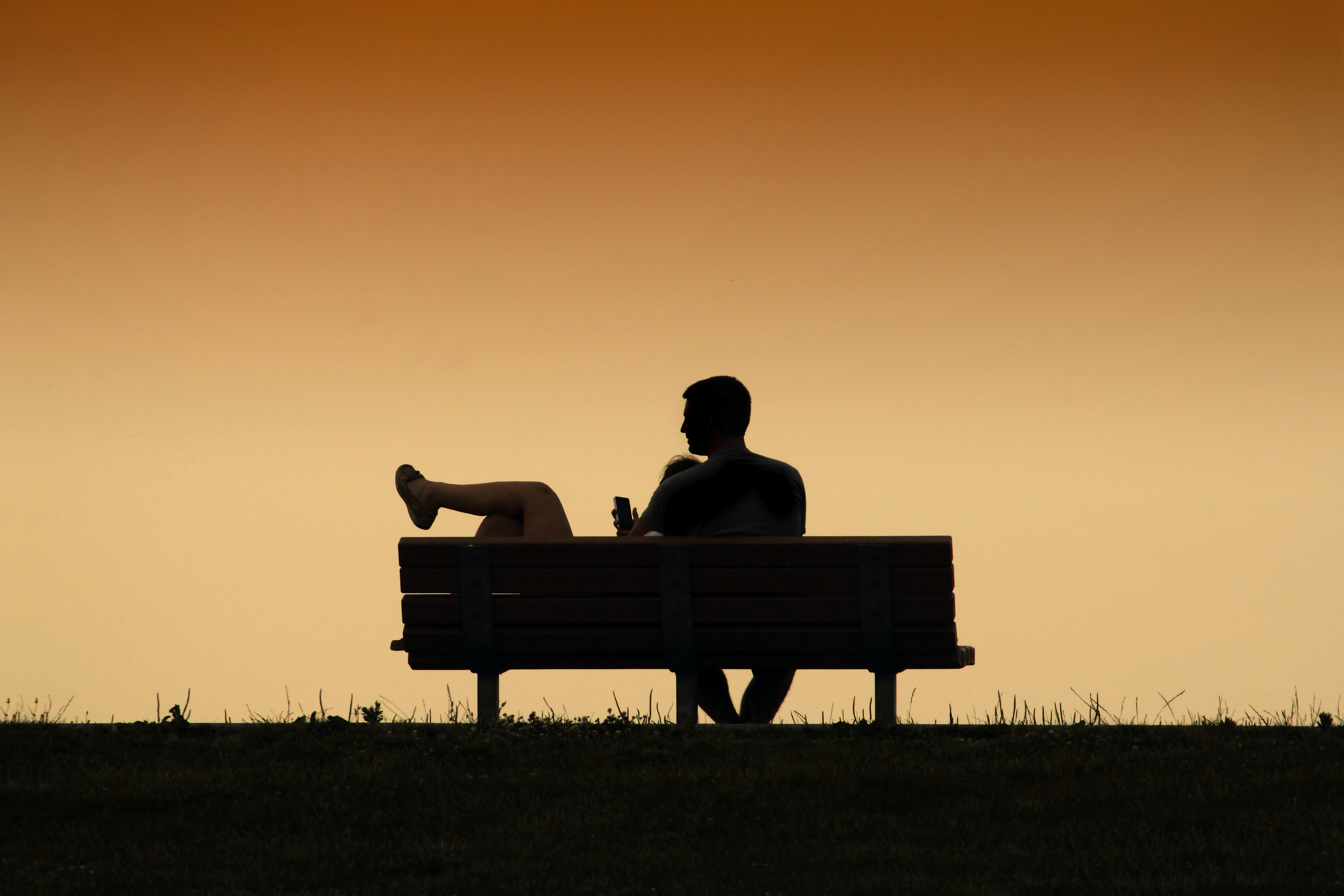 A silhouetted couple embracing on a park bench at sunset in Maumee Bay State Park