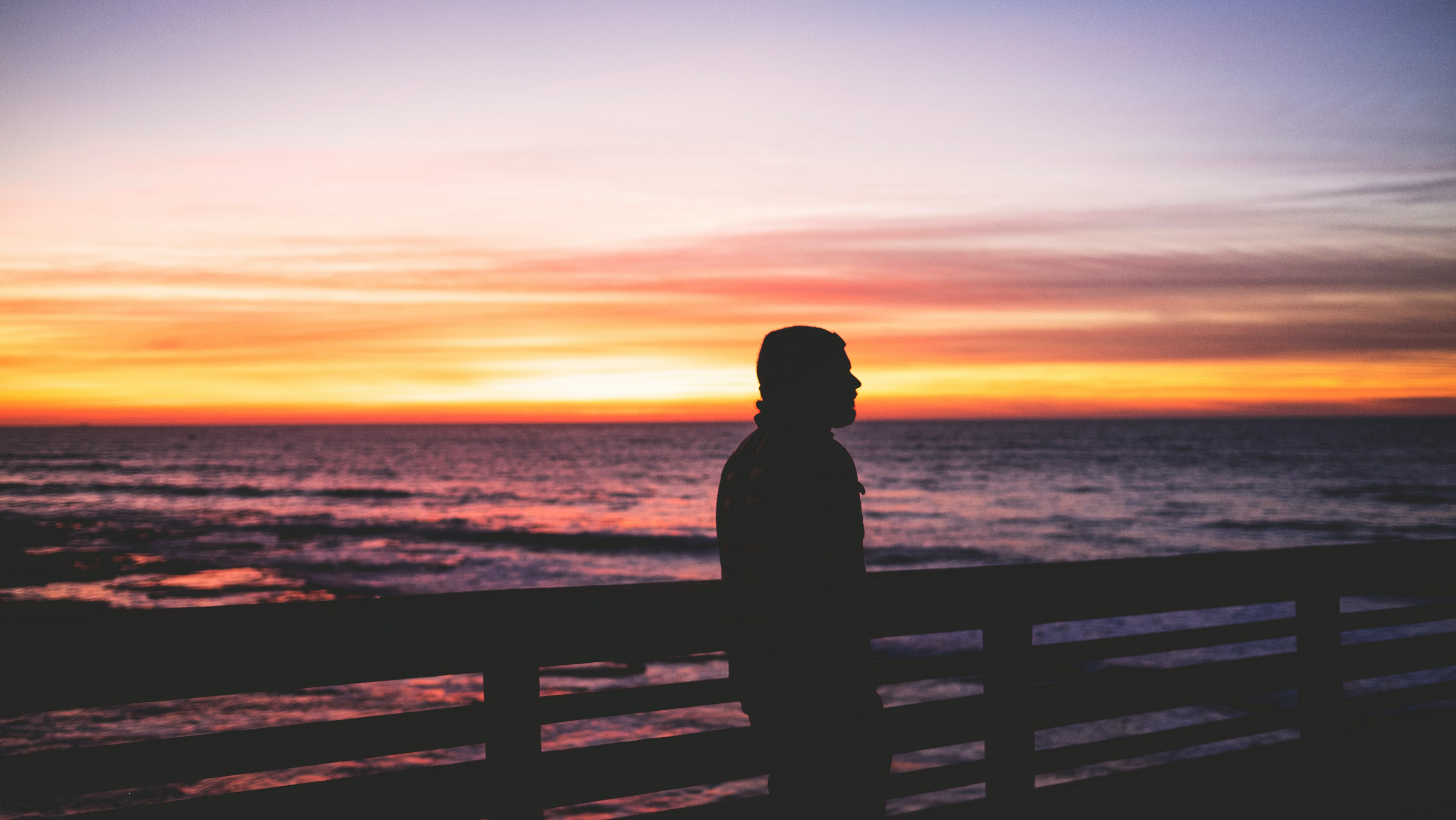 Silhouette of a man looking into the distance, while leaning against a fence by the ocean at dusk
