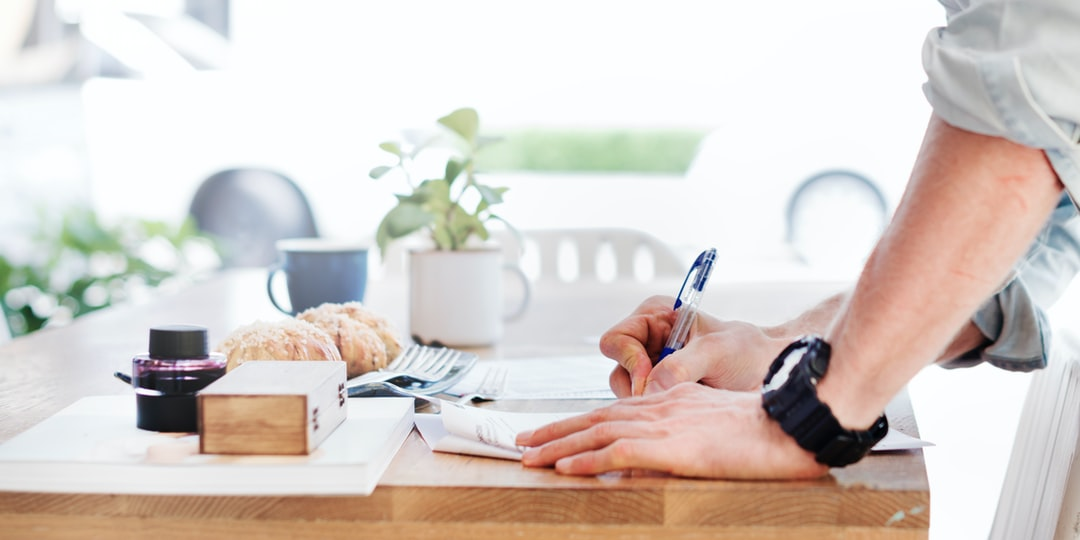 A standing man writing on sheets of paper on a desk with a cup and pastries