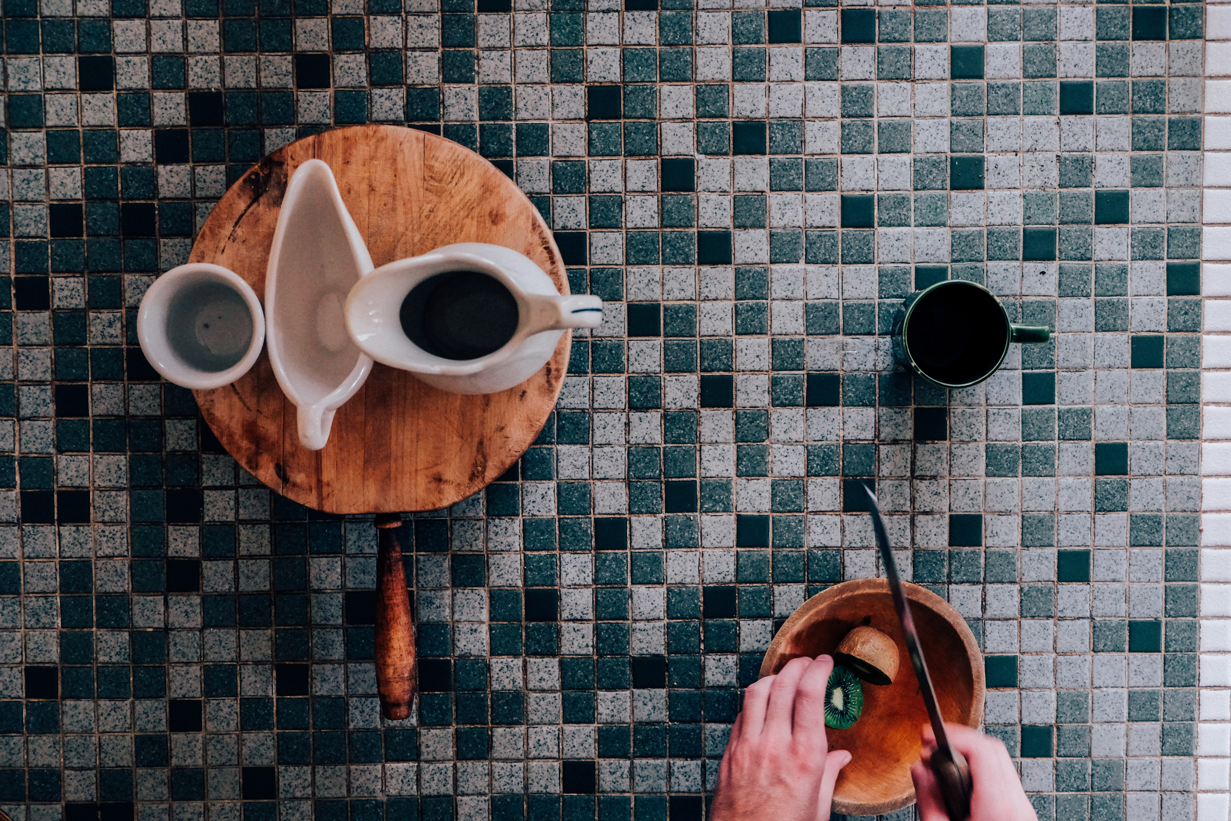 A coffee mug and other cupware on a wooden pan on top of a mosaic chopping board