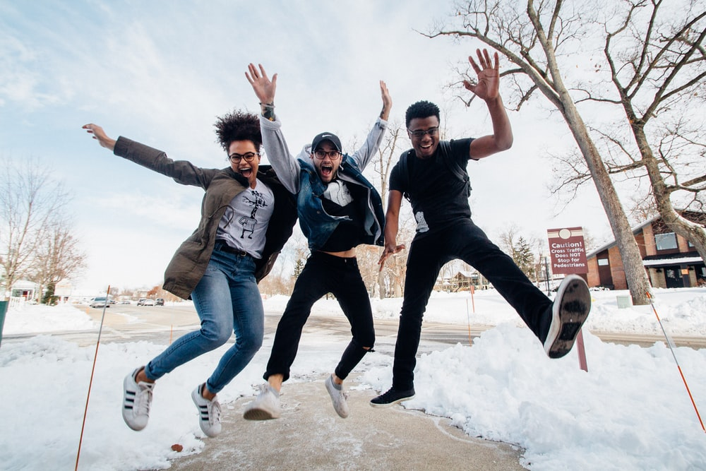photo of three men jumping on ground near bare trees during daytime