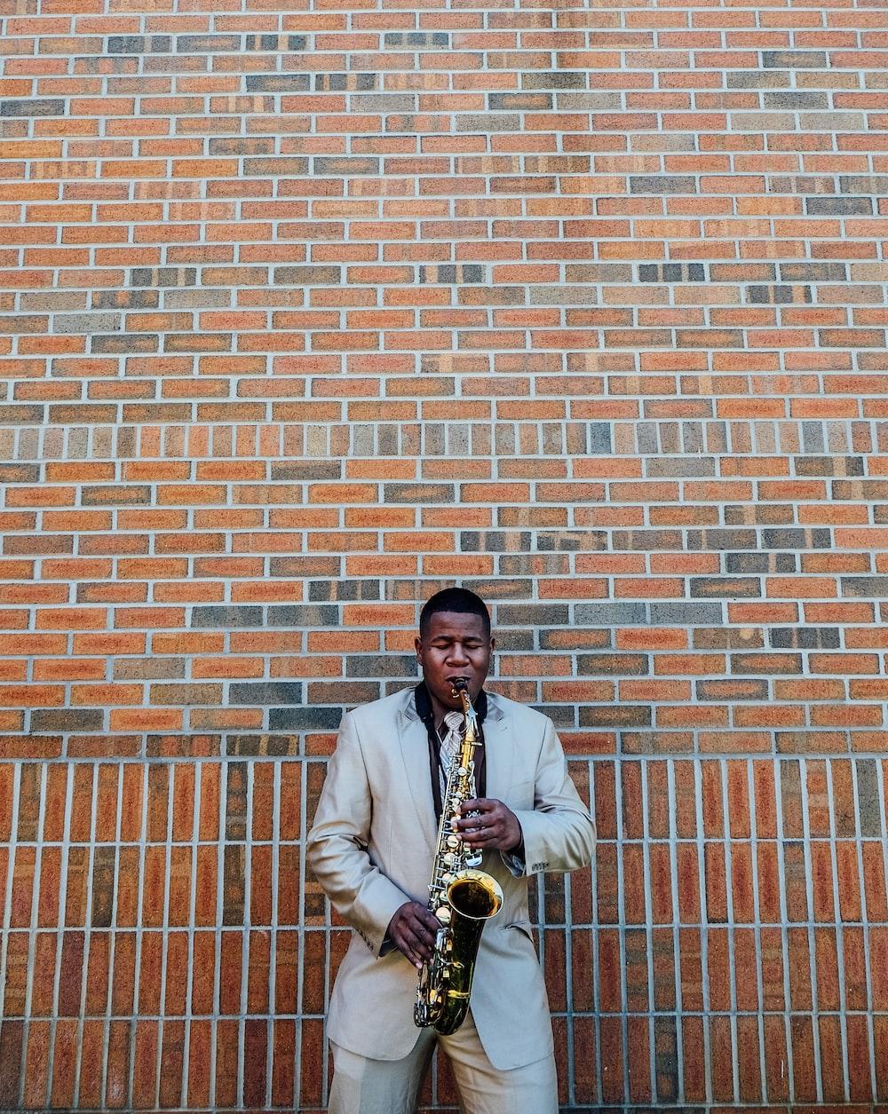 man playing saxophone near concrete brick