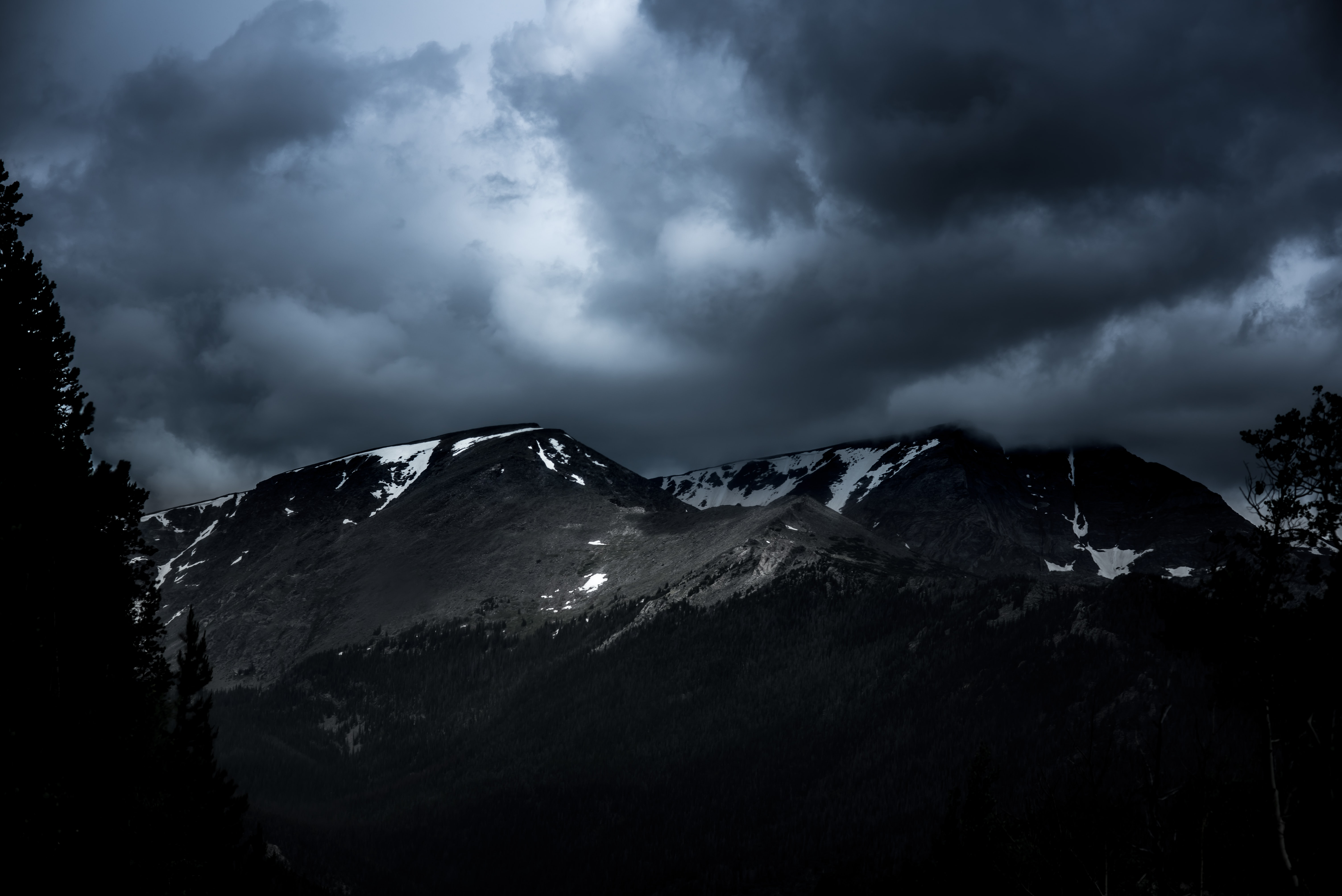 A dark cloudy overcast on snow covered mountain tops.