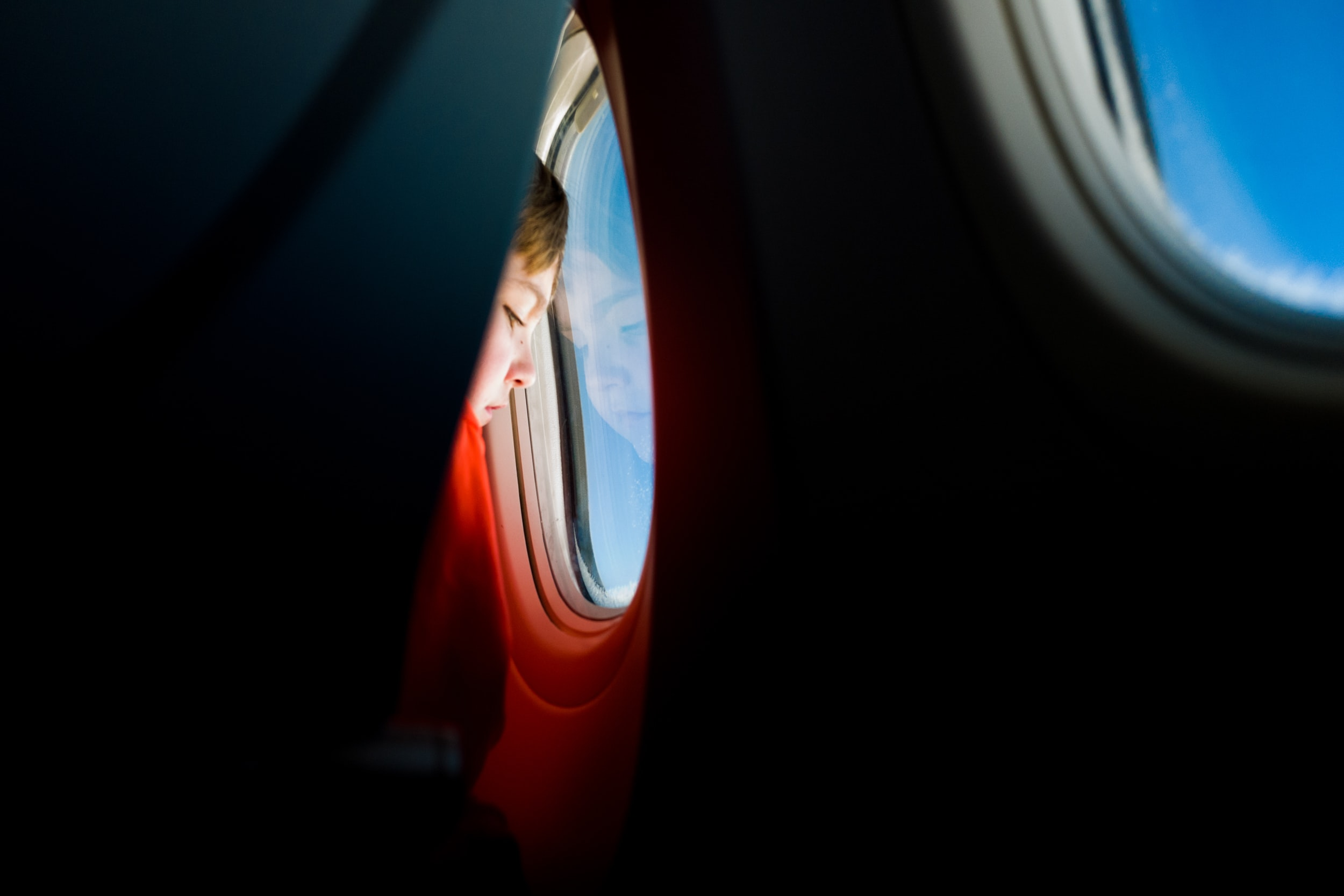 A child presses his forehead against the window of a flying plane