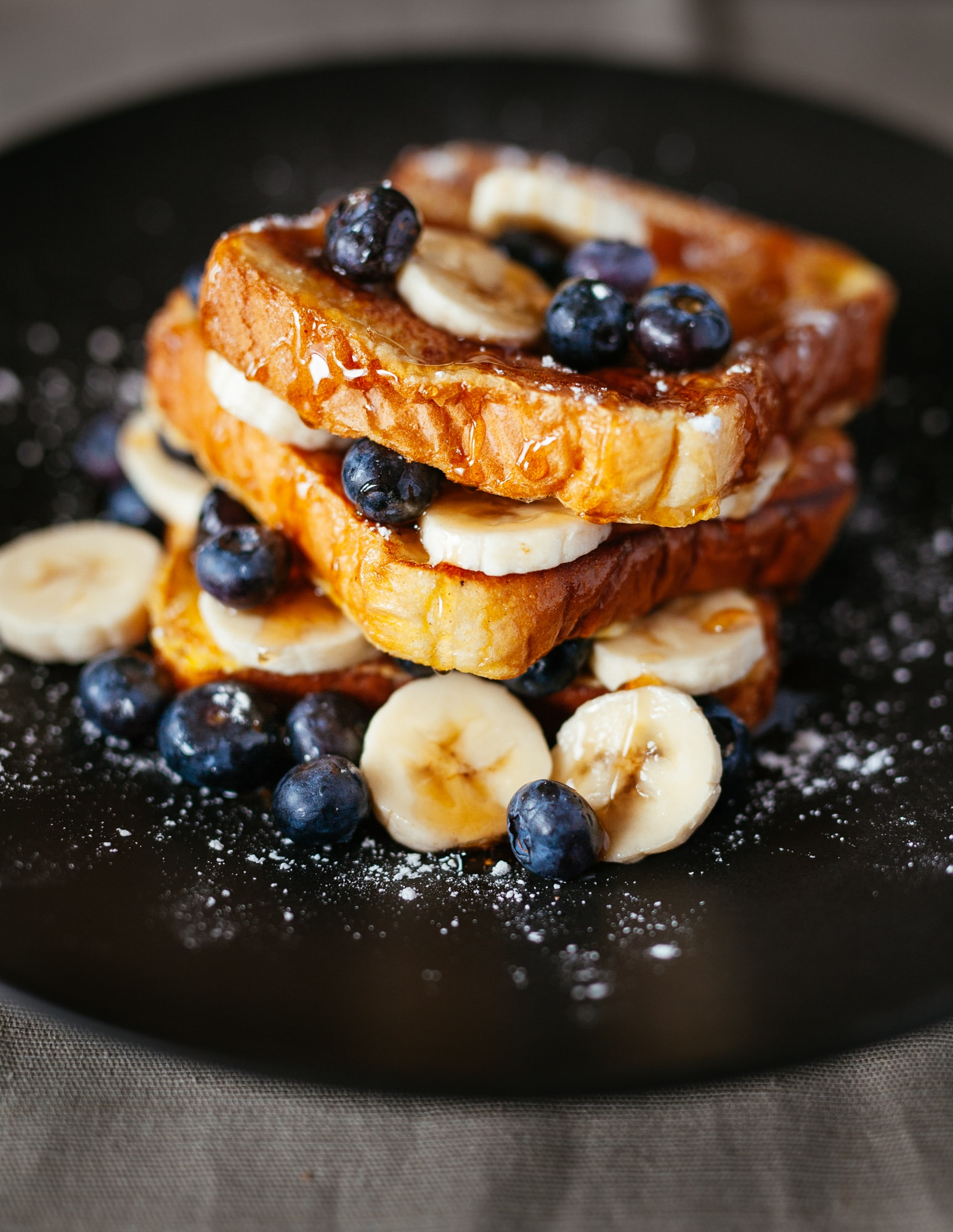 Sweet french toast with syrup, bananas, and blueberries for breakfast