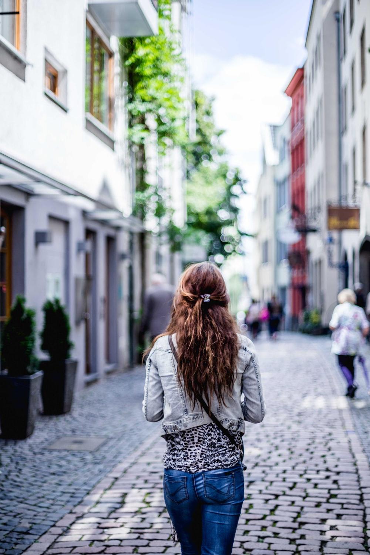 woman wearing gray top walking on sidewalk during daytime