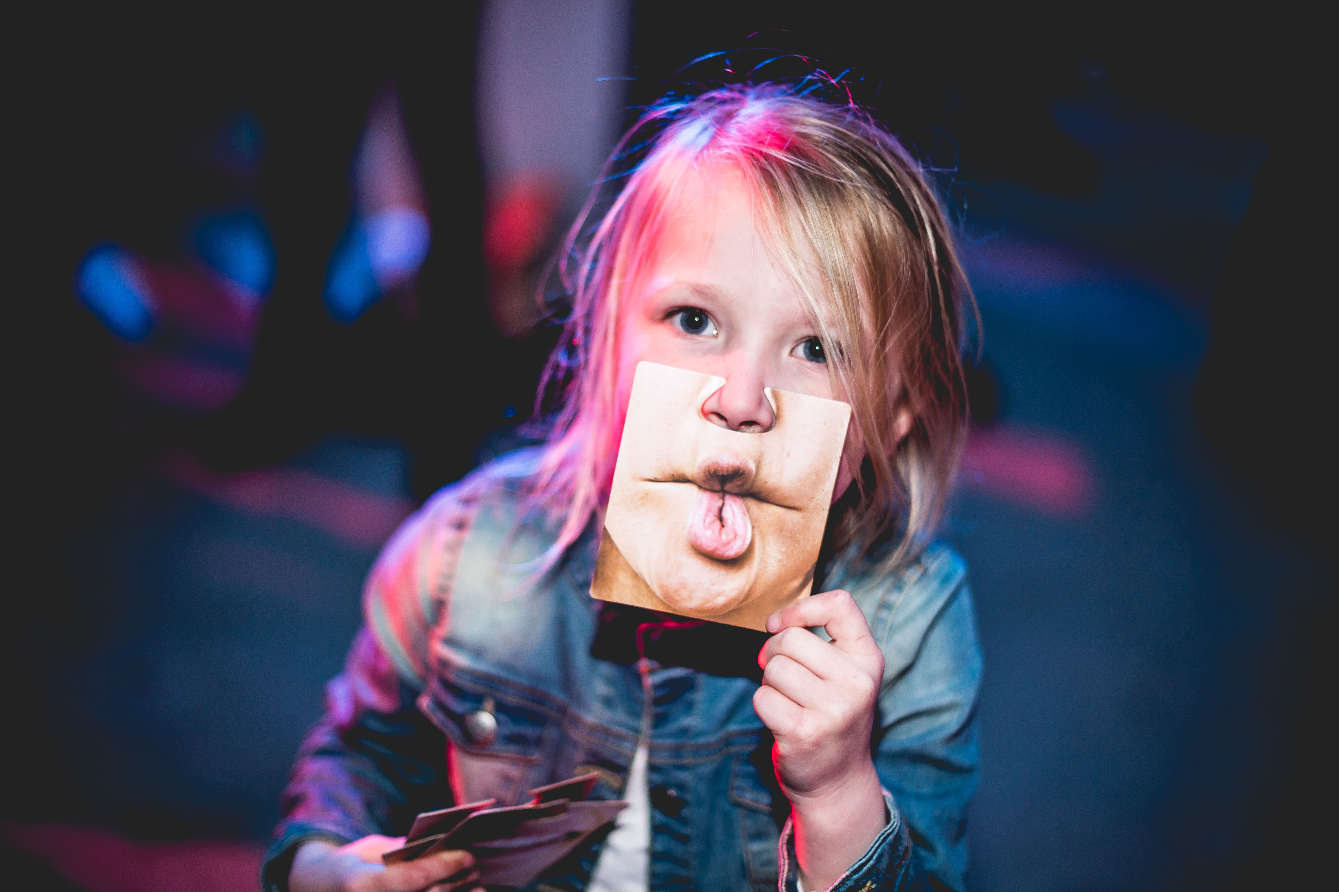 A child holds a picture of puckered lips in front of her face in Sliedrecht