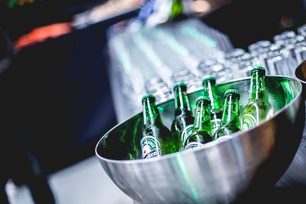 green glass bottles in stainless steel bowl