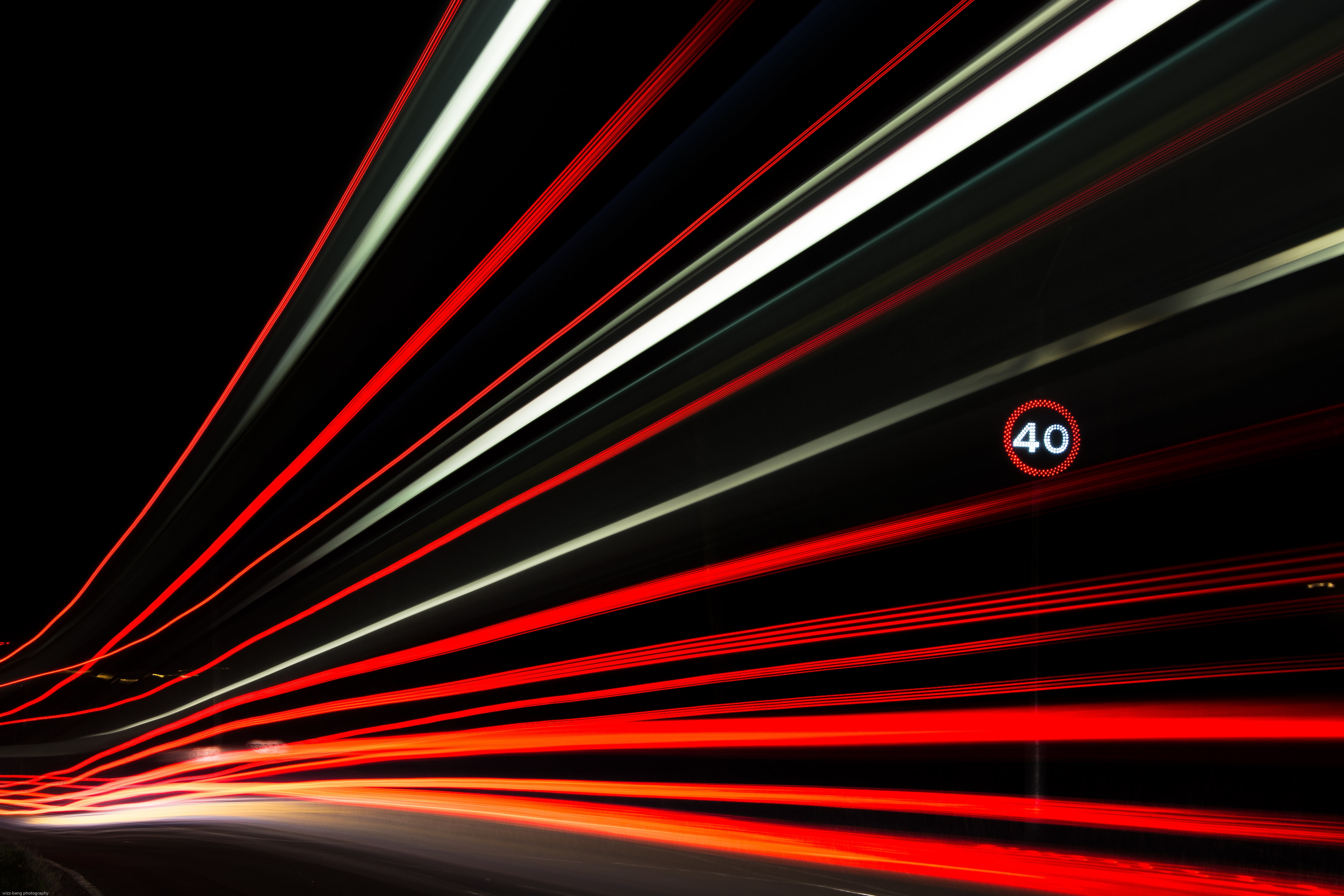 A long exposure shot of car taillights trailing in a timelapse down a dark road