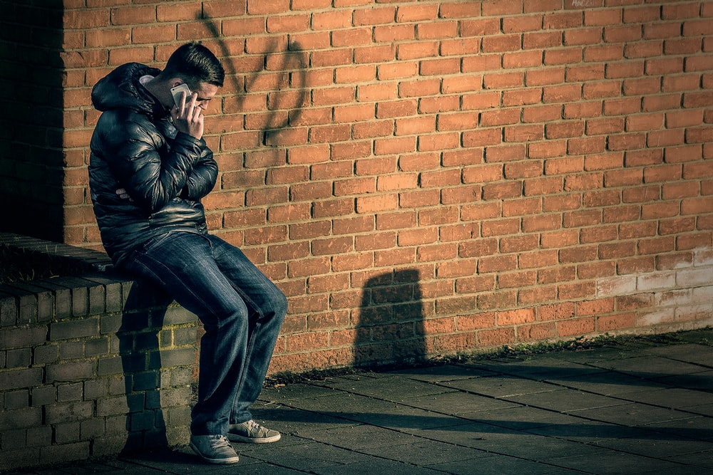 man in black leather jacket sitting on brick wall holding smartphone