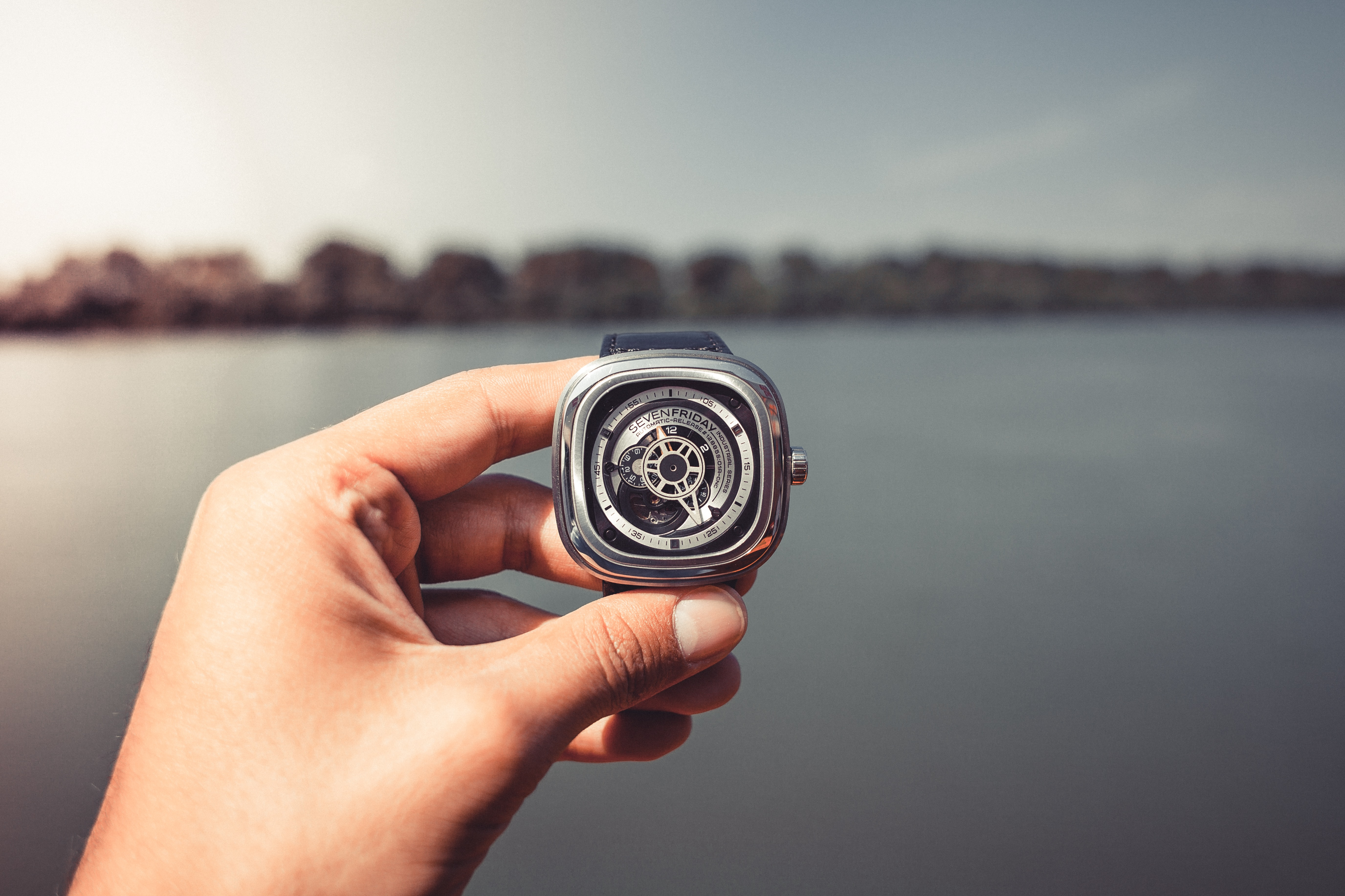 Hand holding a modern watch with gears showing in front of a city skyline and water