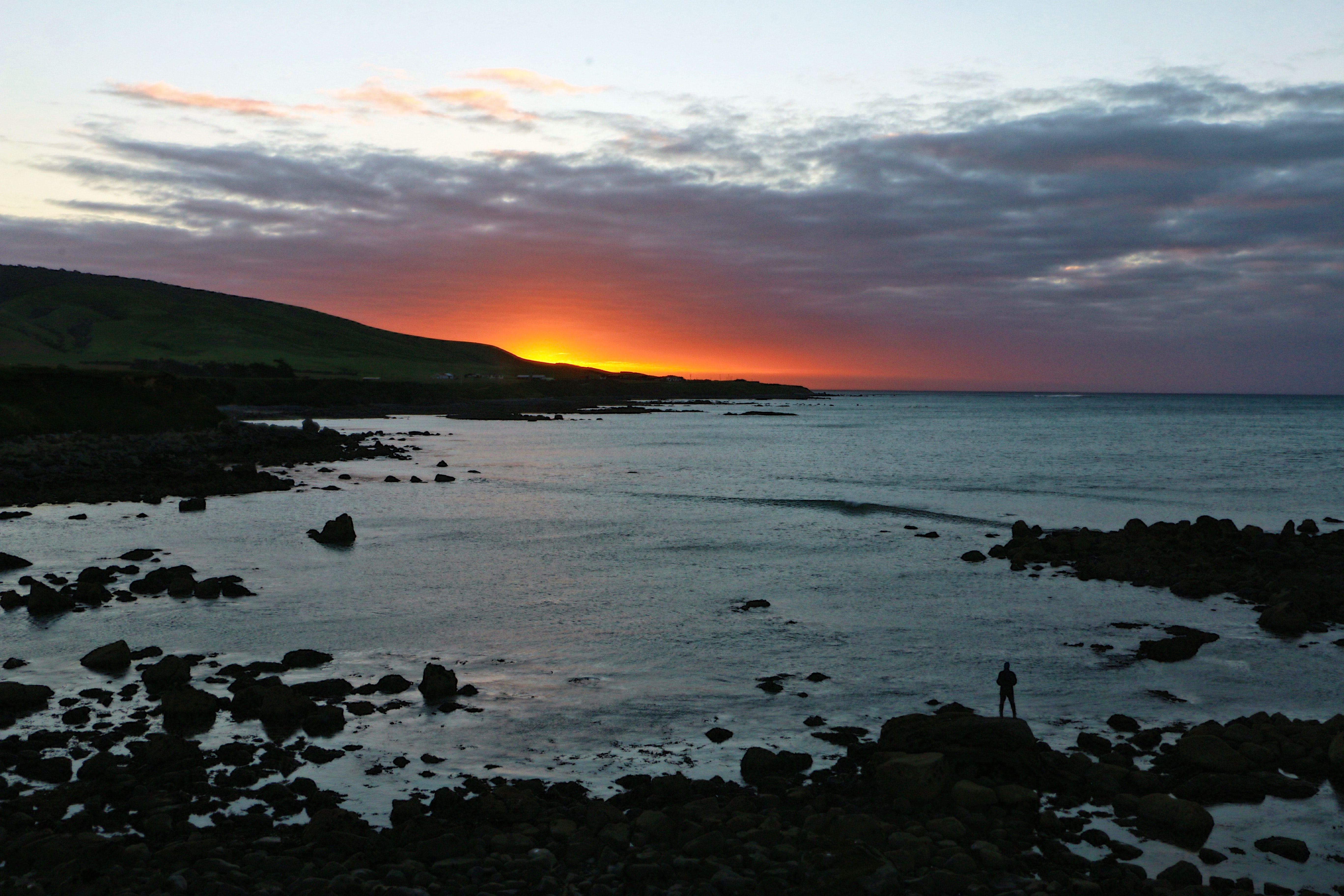 Distant shot of a person standing on a rocky beach as clouds gather, sun sets behind a far mountain