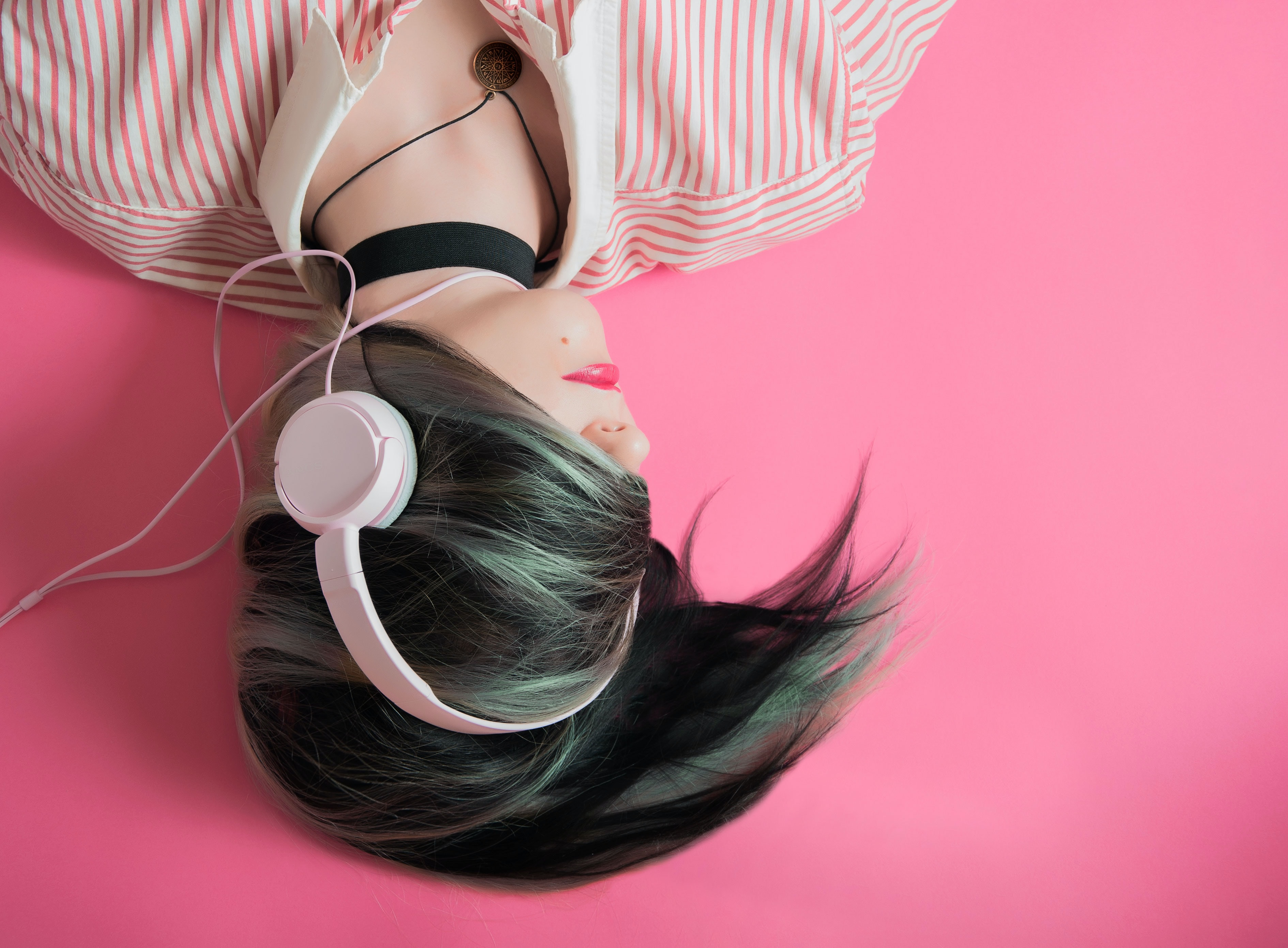 A dark-haired woman with her hair wrapped around her hair listening to music on headphones