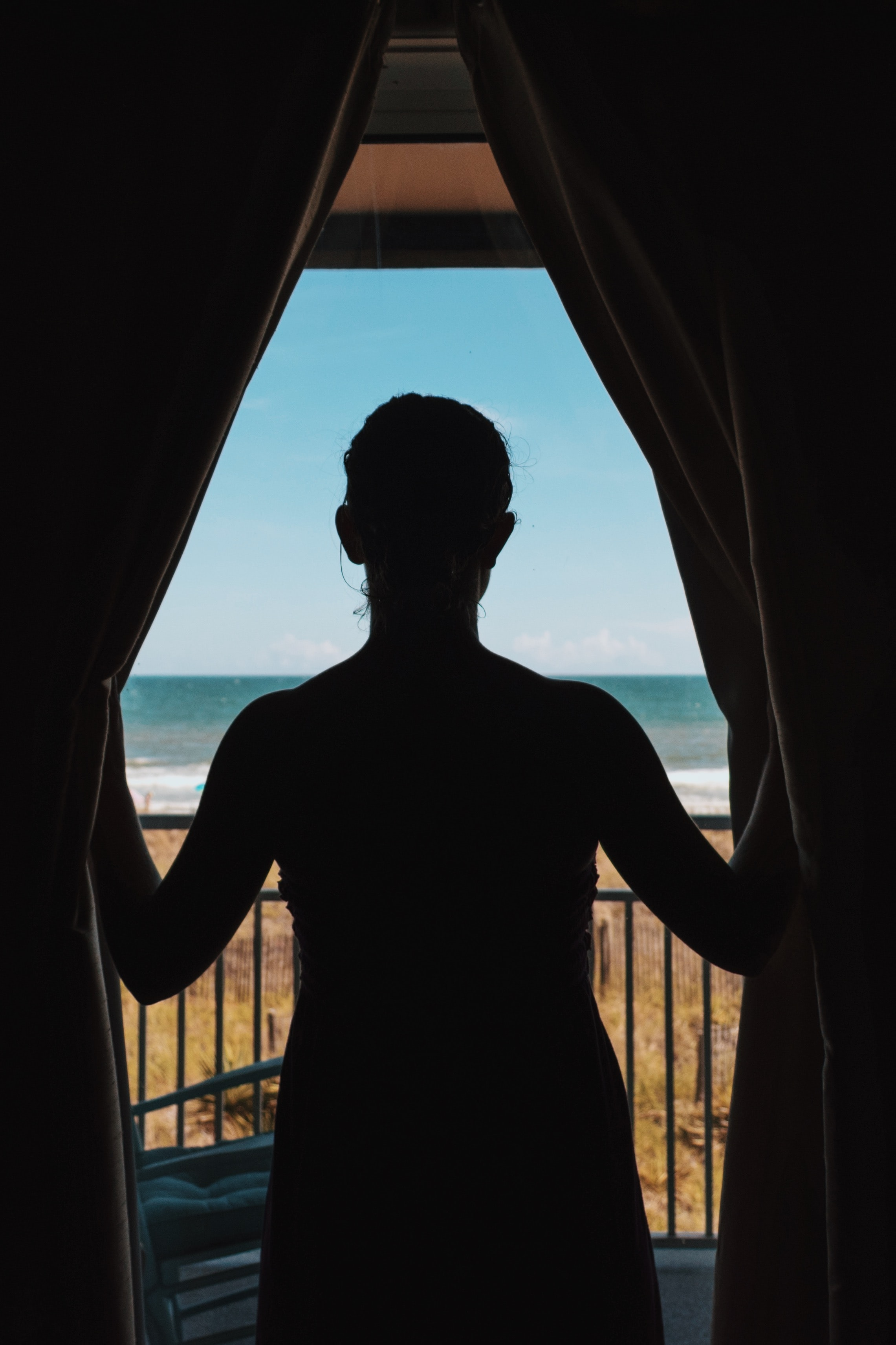 silhouette photo of woman standing between curtains