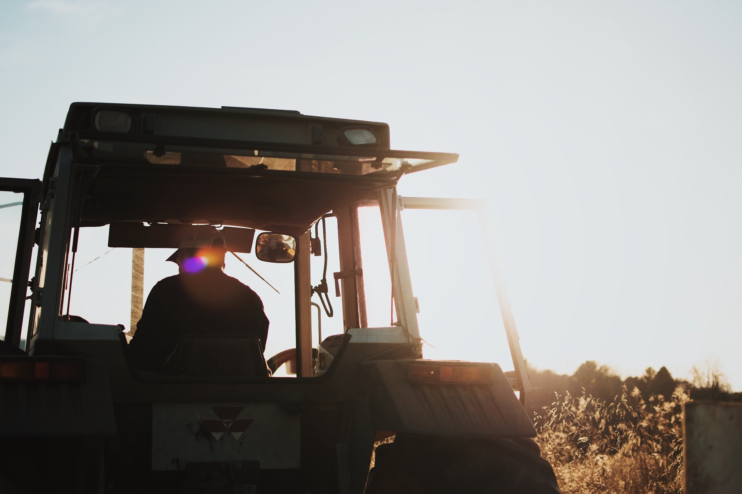 silhouette of man riding tractor