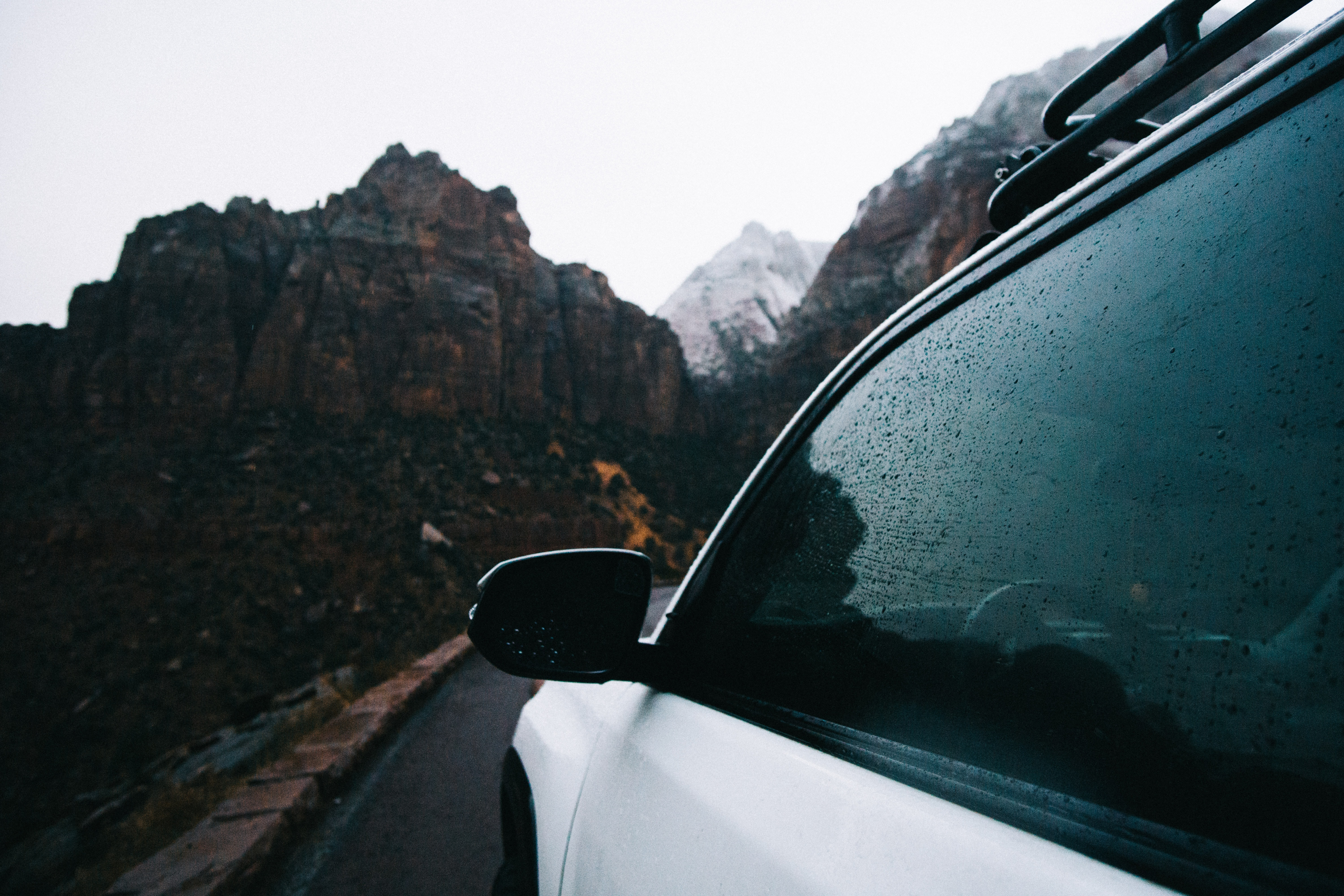 White vehicle driving down a mountain road in a driver's side POV.