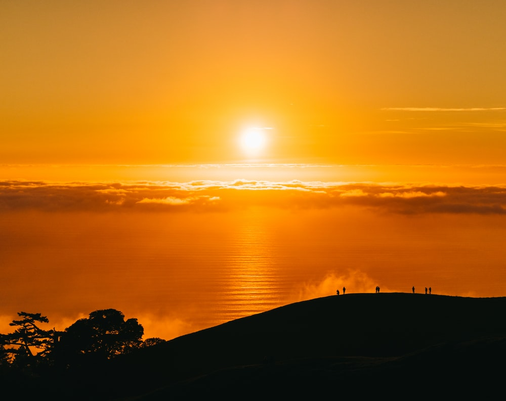 people on top of hill under white clouds golden hour photography
