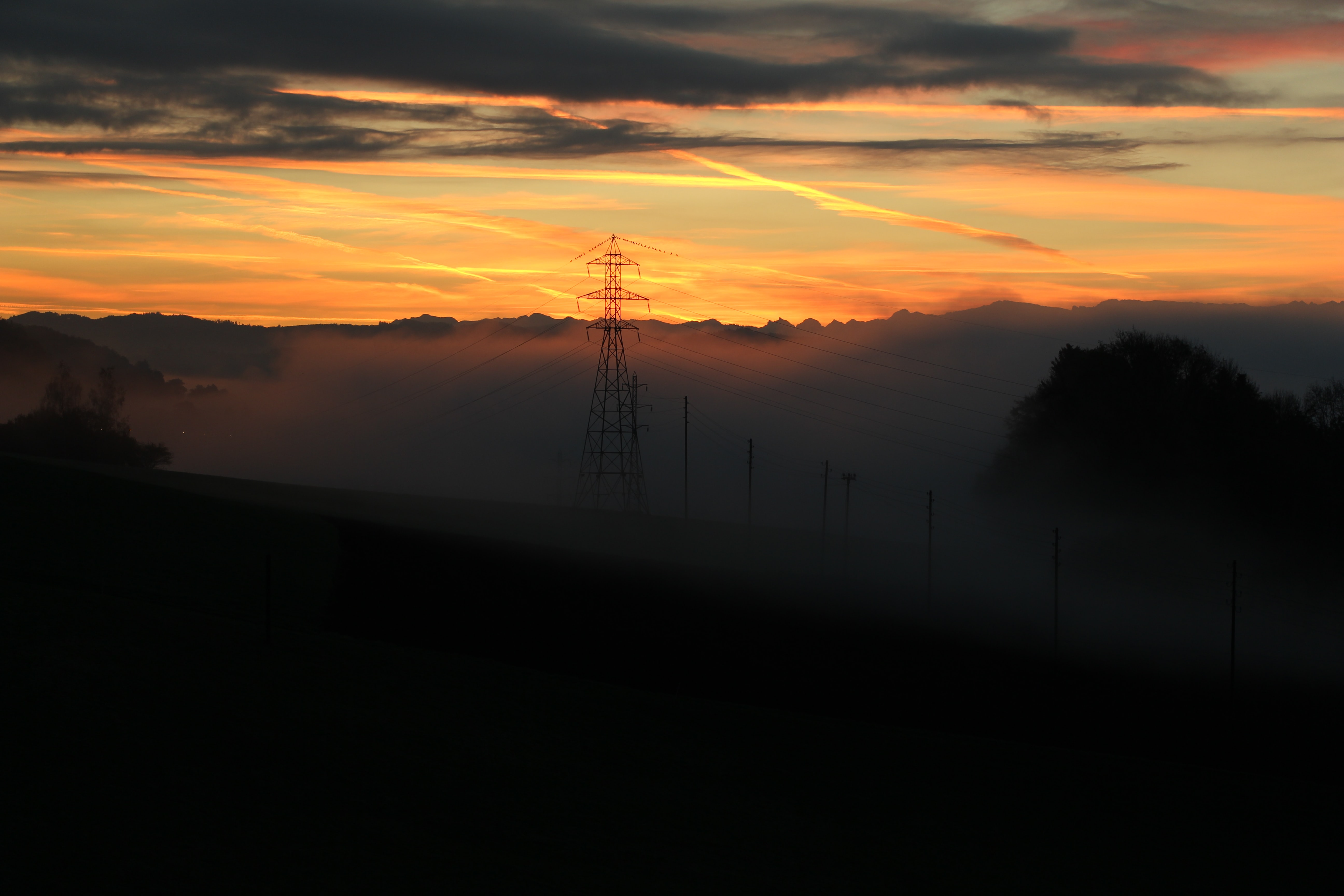 Pylons in the distance of a cloudy sunset scene in Bern