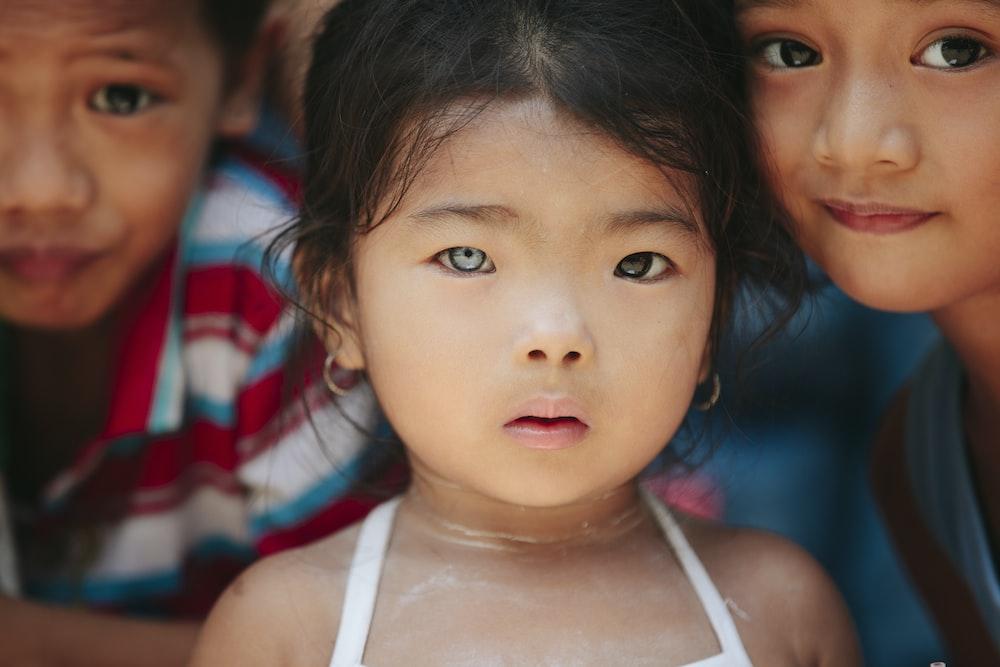 girl standing beside children