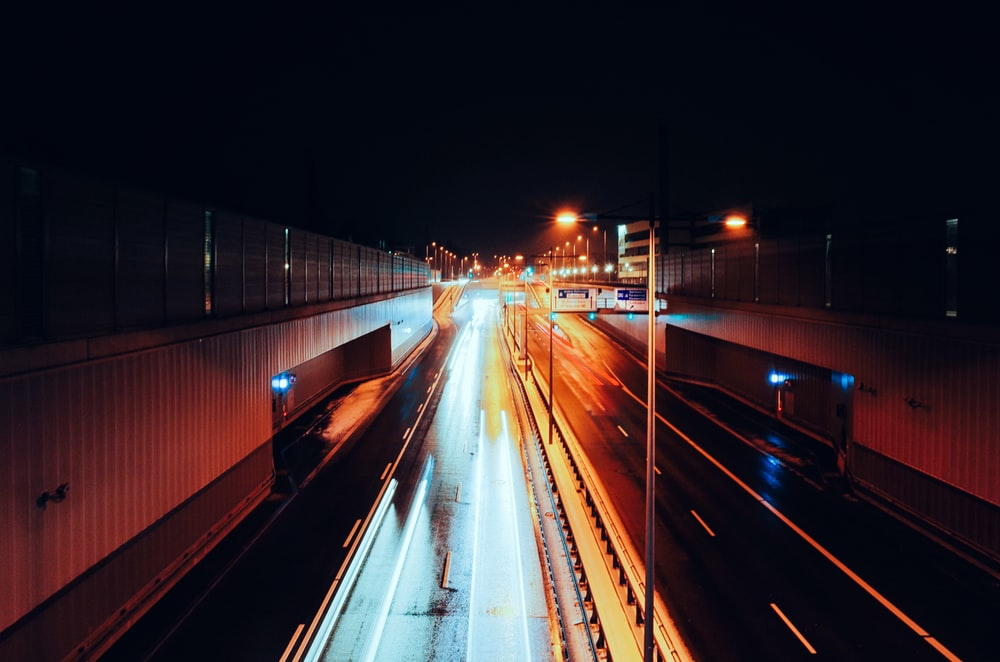 empty road with streaks of light during nighttime time lapse photography