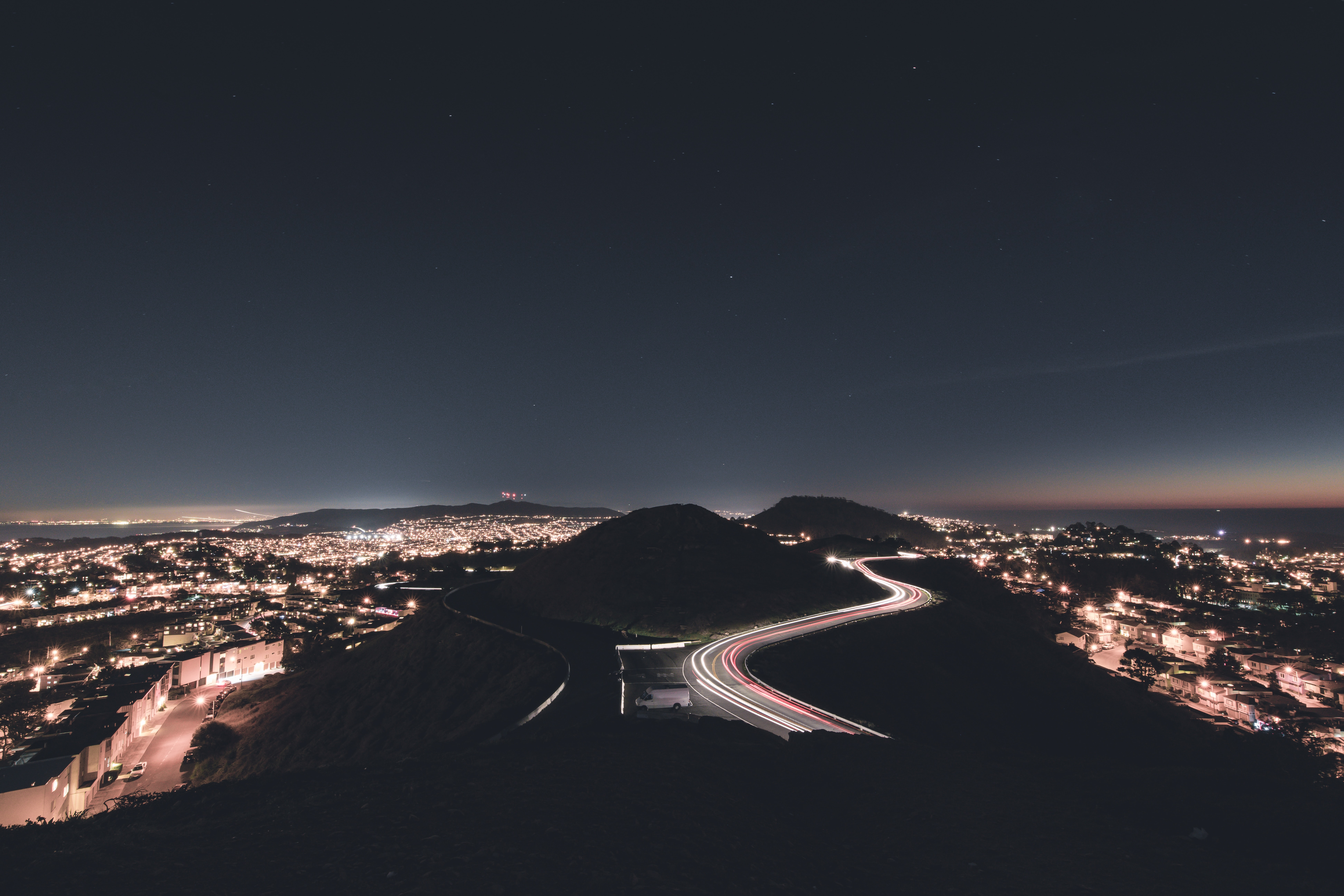 A cityscape image of Twin Peaks, featuring a light trail timelapse on a local road