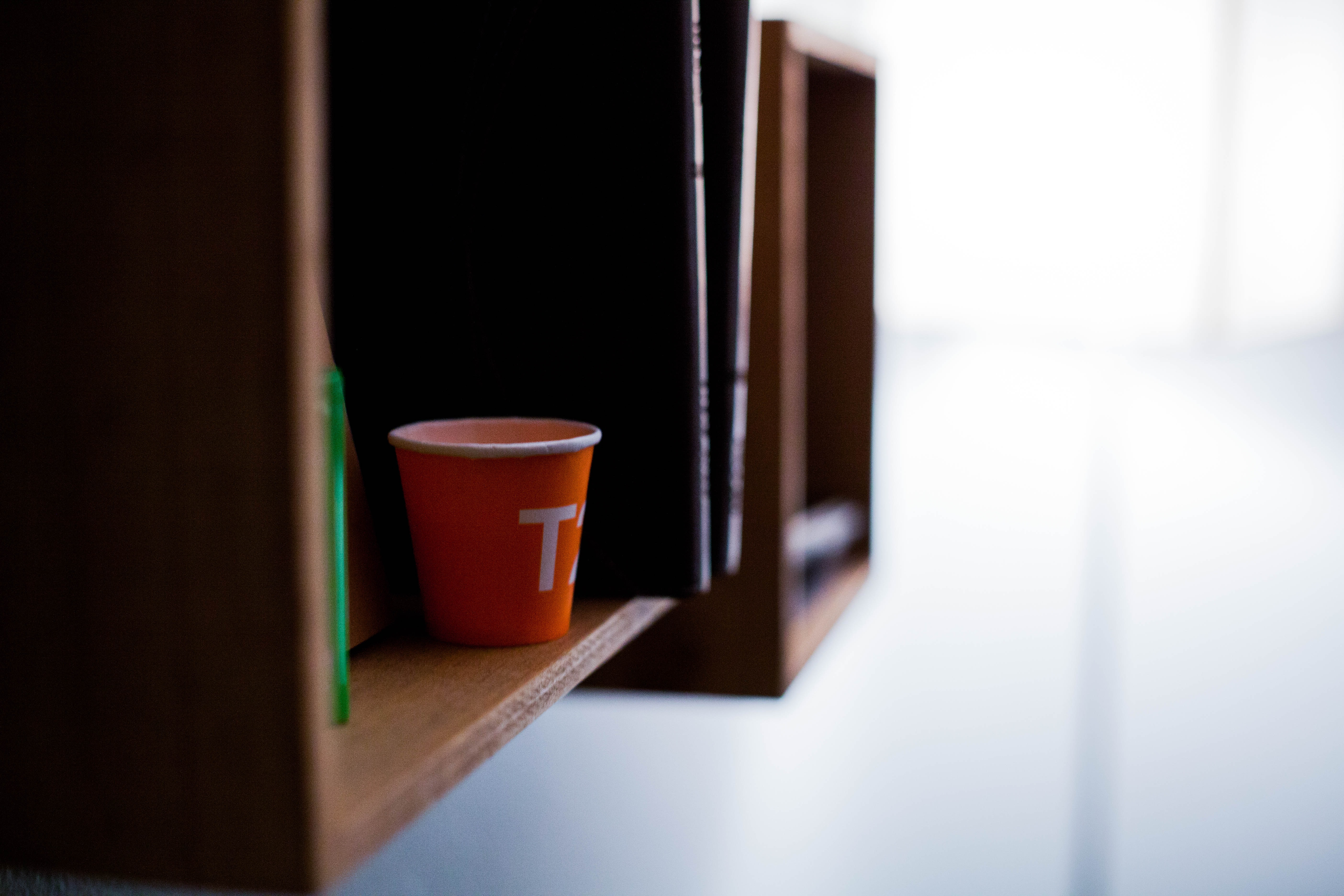 Orange T cup on a wood bookshelf at home