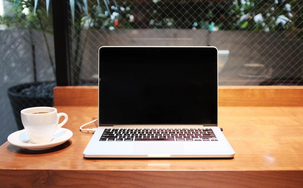コーヒーマグの横にあるラップトップコンピューター