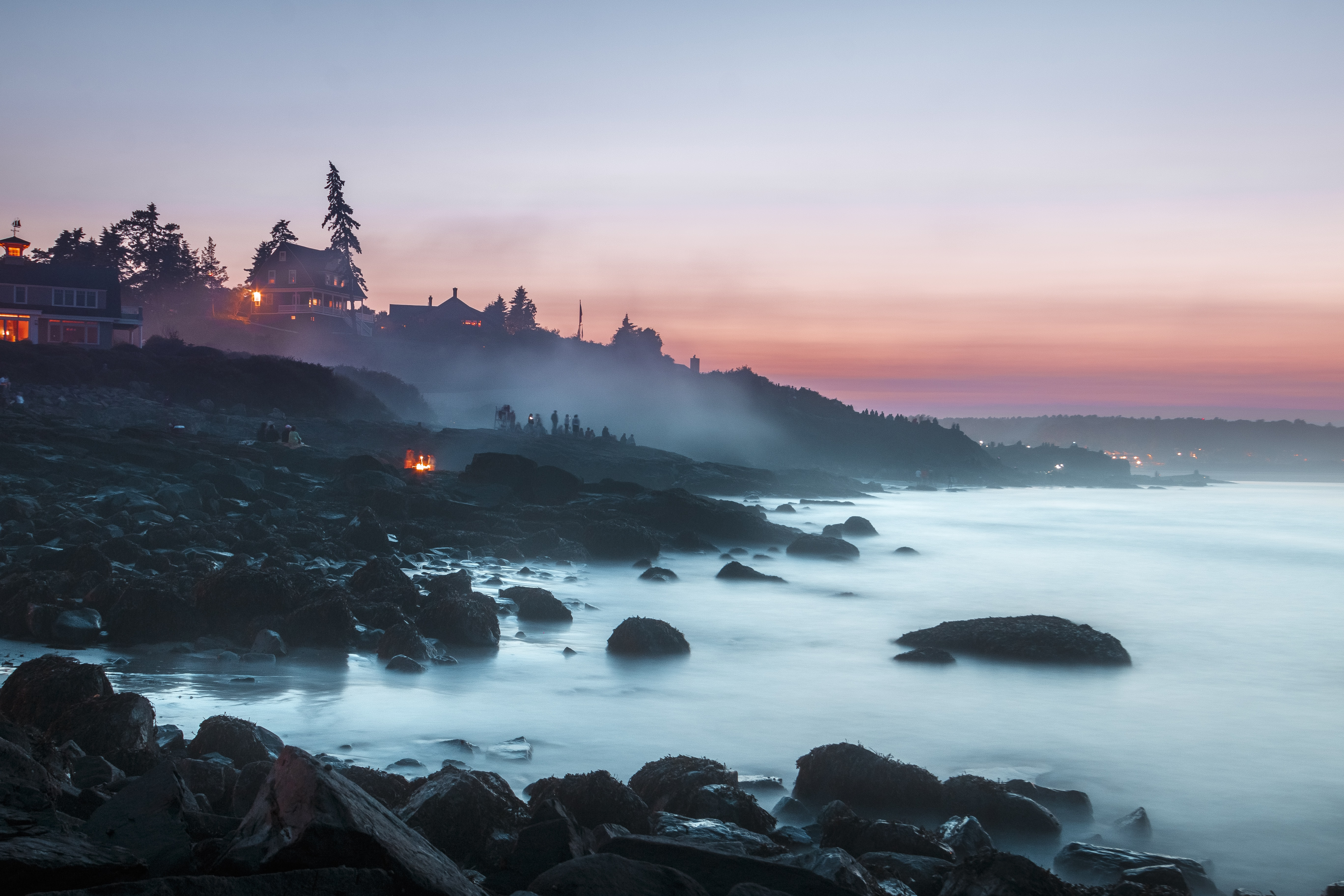 Sunset on a rocky coastline of Ogunquit where groups of people are watching an ocean mist rising from the waters