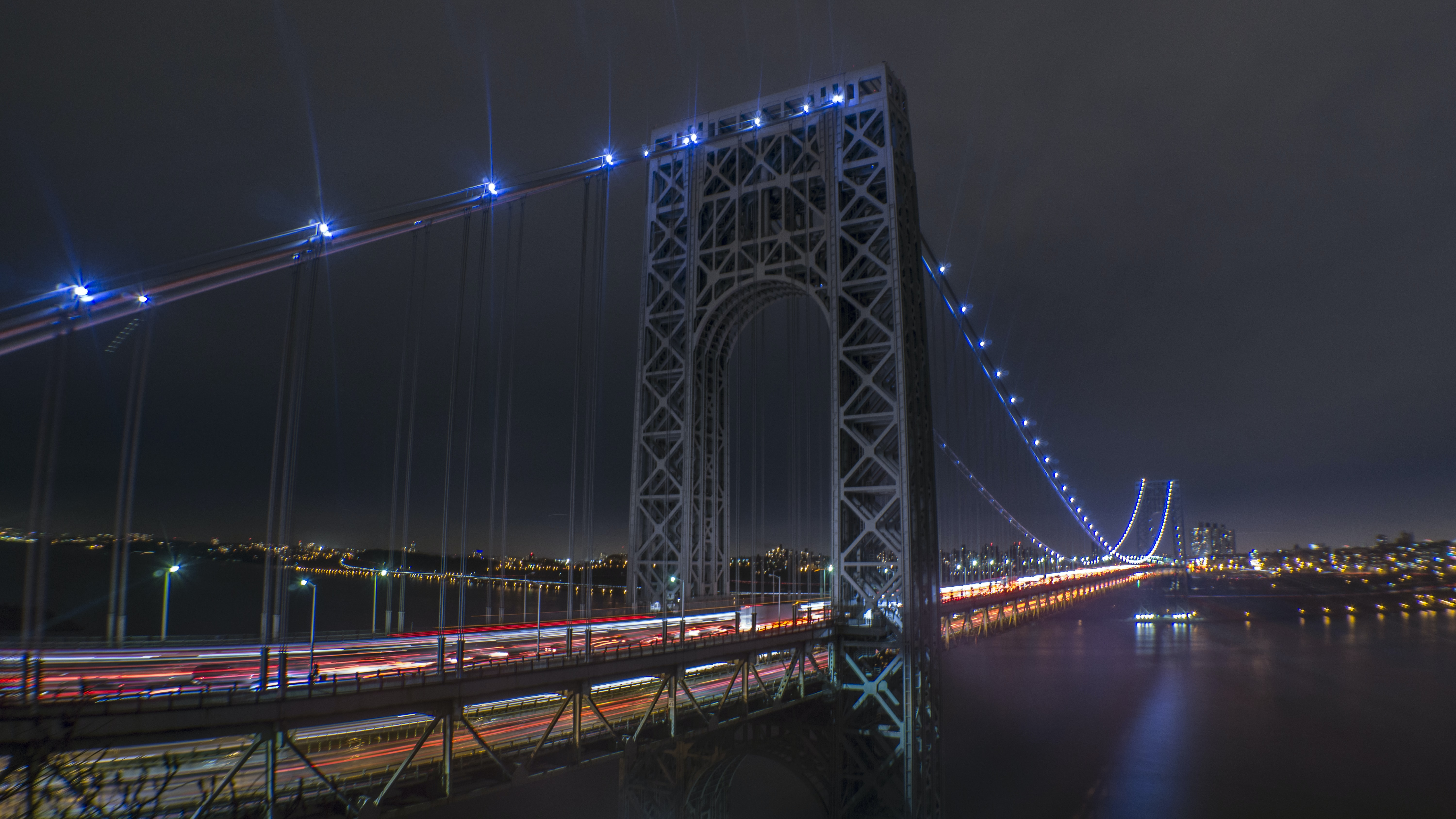 A close-up view of a bridge illuminated with blue lights, taken from the city's skyline