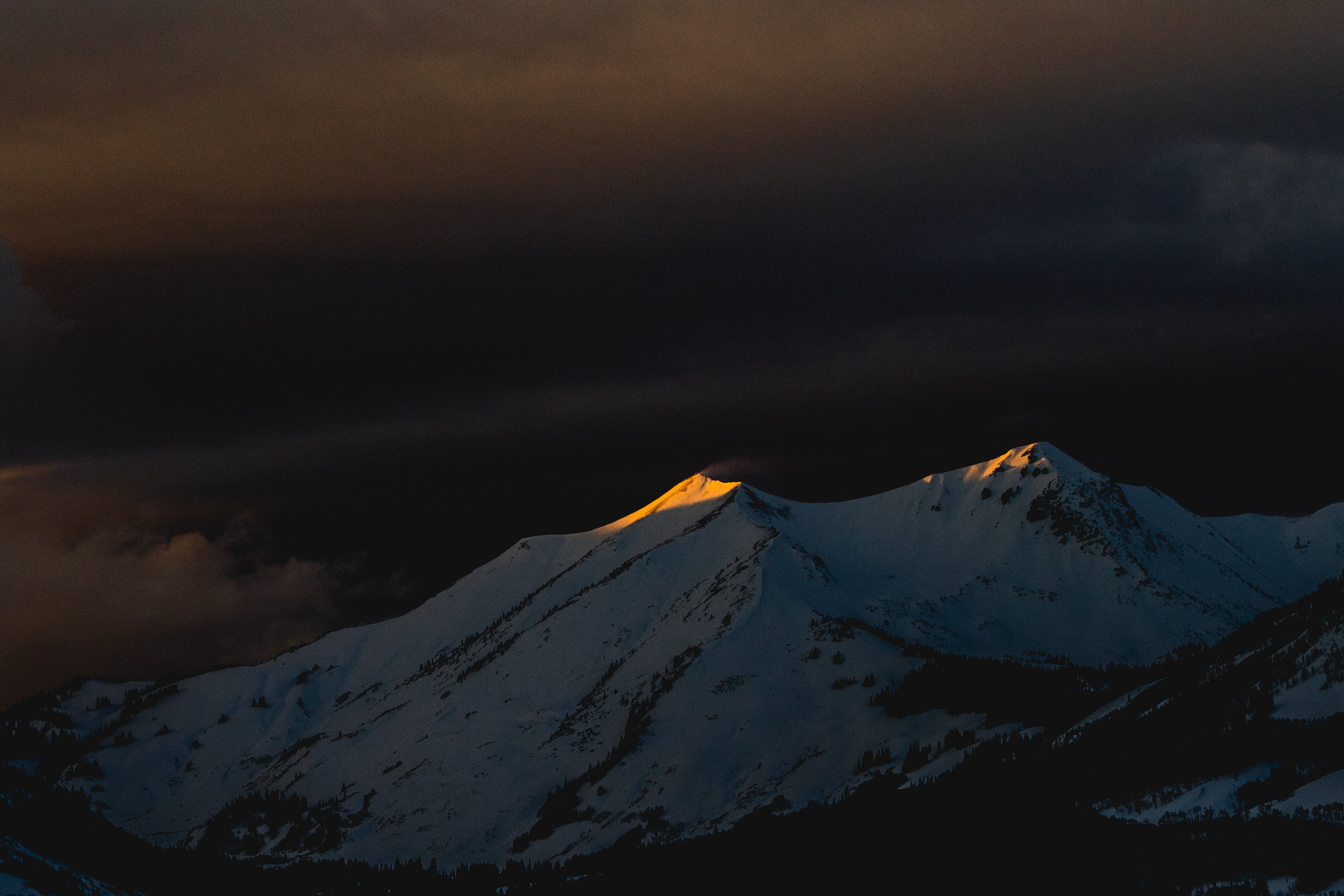 The last rays of sun on the peaks of a snowy mountain at dusk