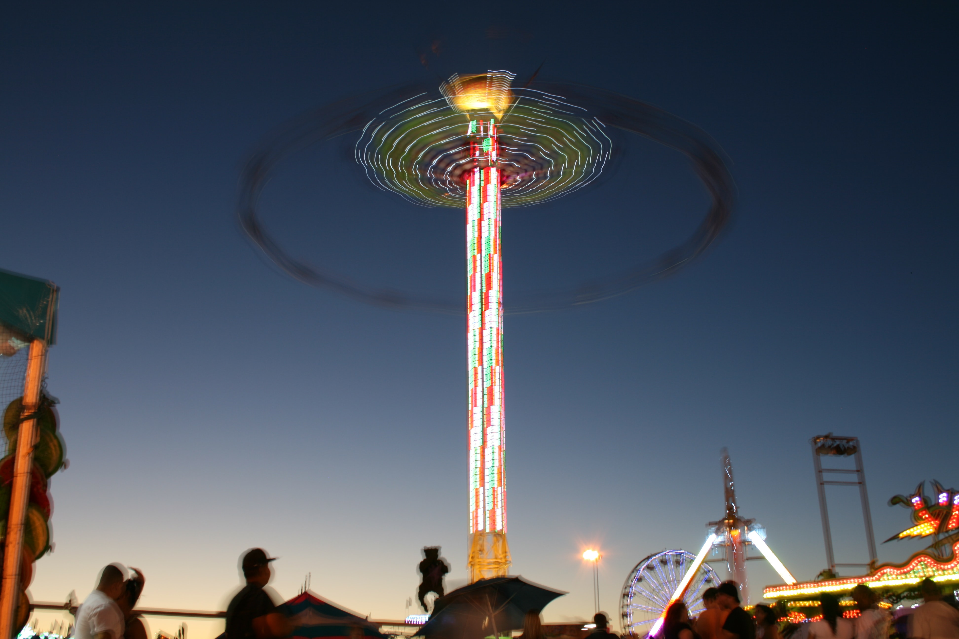 Long exposure of swing ride at Cal Expo glowing in the night with fair goers passing by