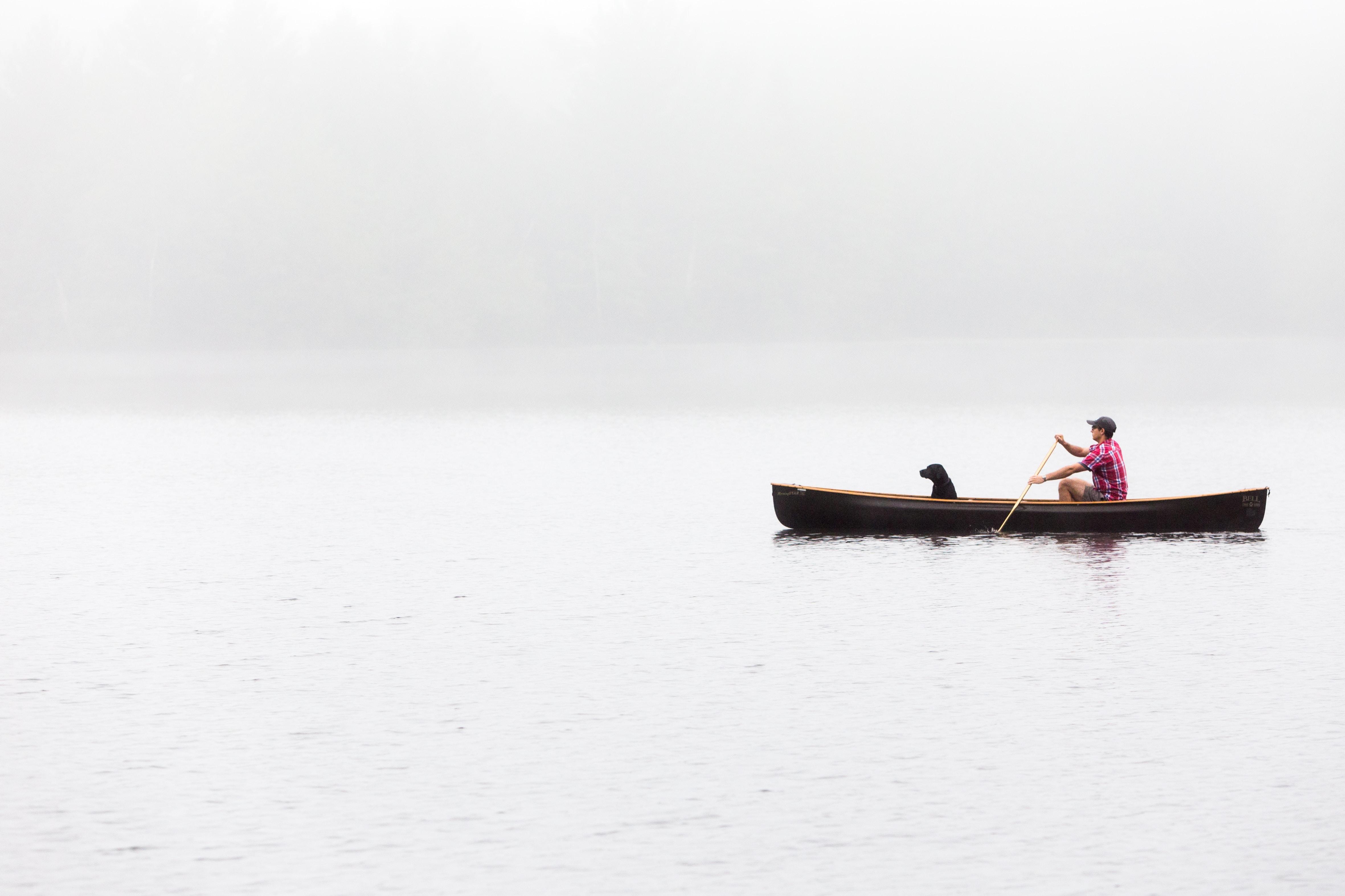 Man and dog on a foggy morning canoe ride through a calm lake
