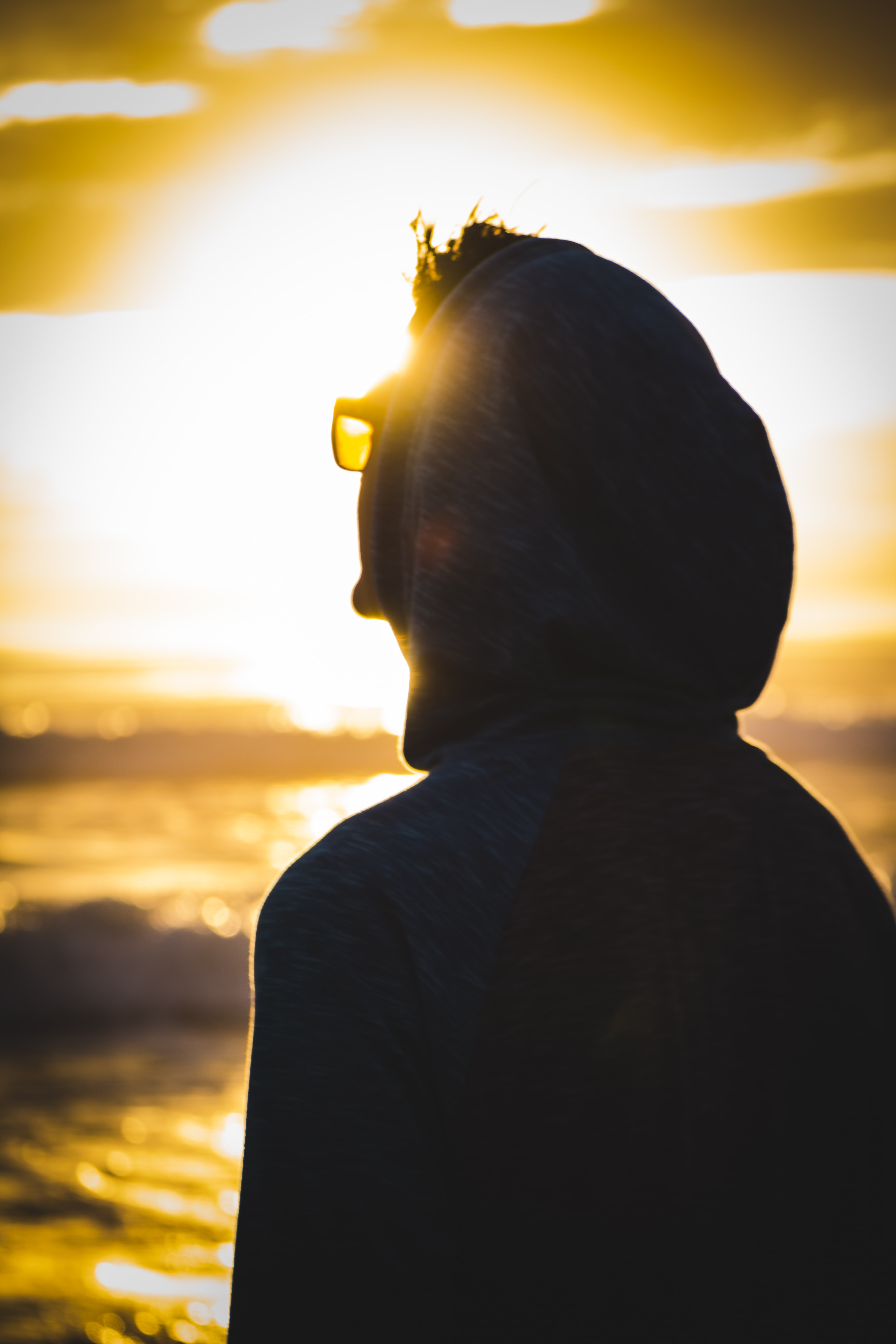 A person in glasses and a hoodie looks toward the bright sun in Malibu