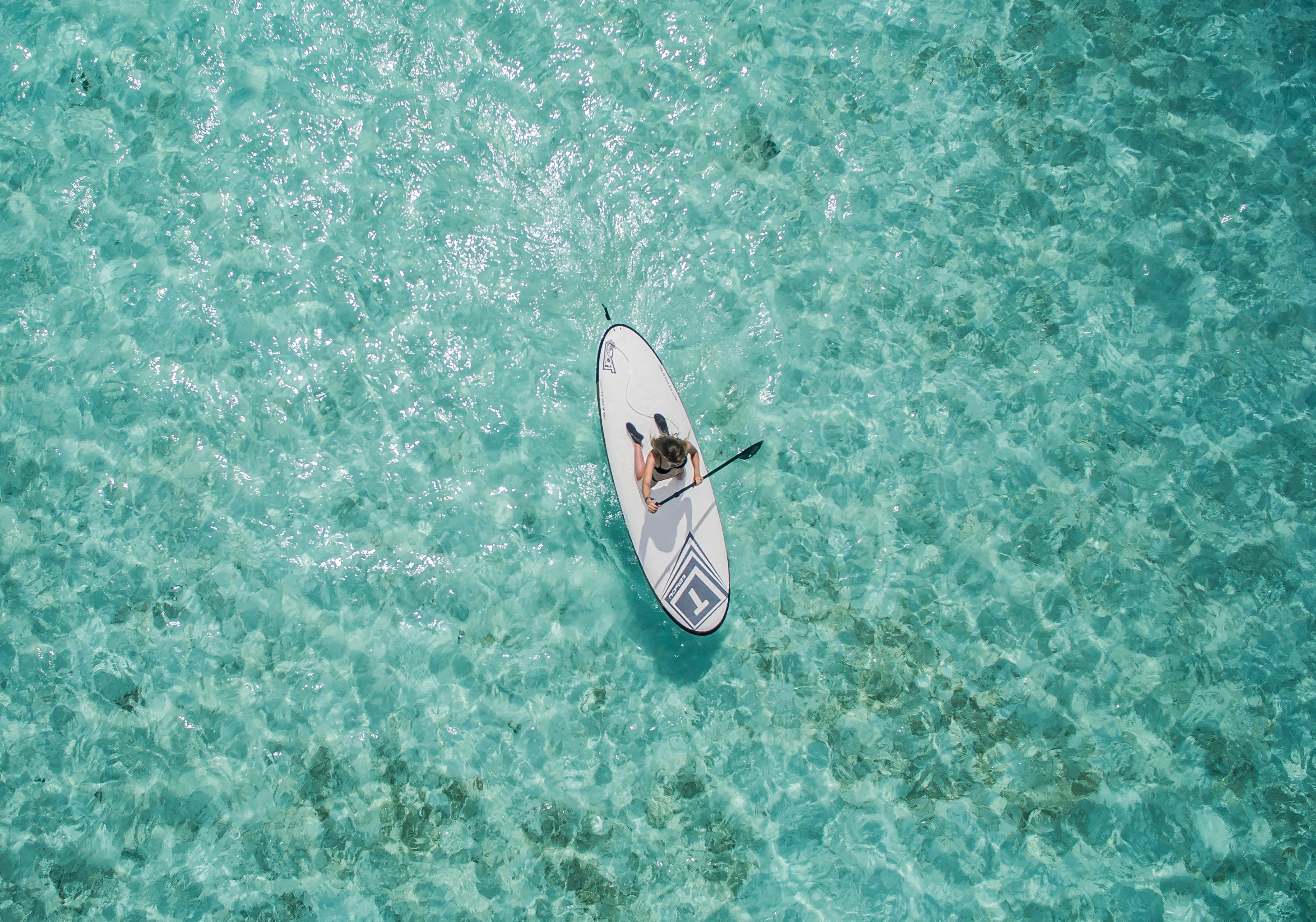 A drone shot of a woman paddling on a white wakeboard on the clear surface of water