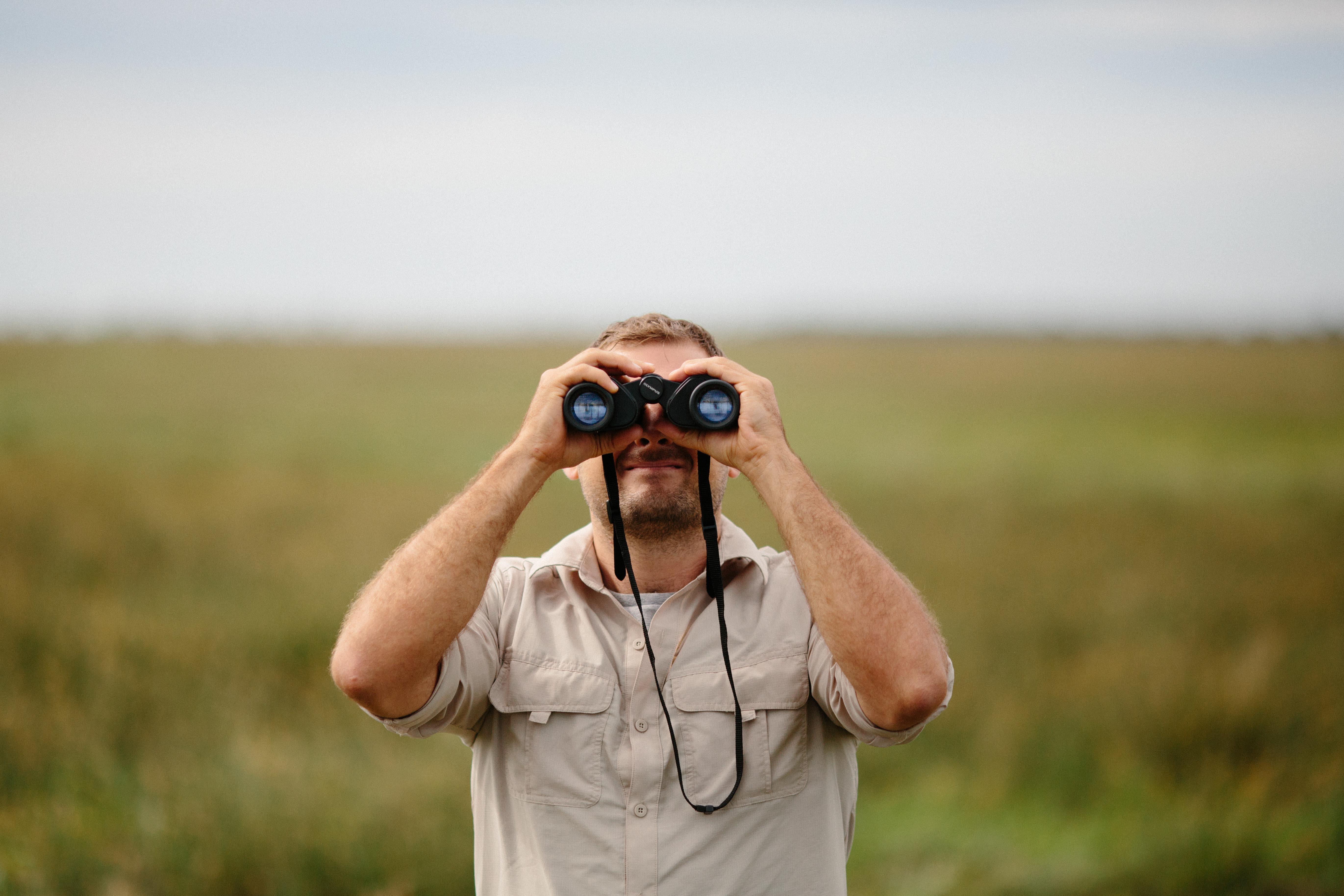 Man on a safari expedition looking through binoculars