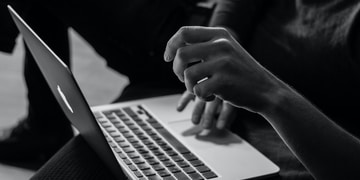 grayscale photo of person using MacBook