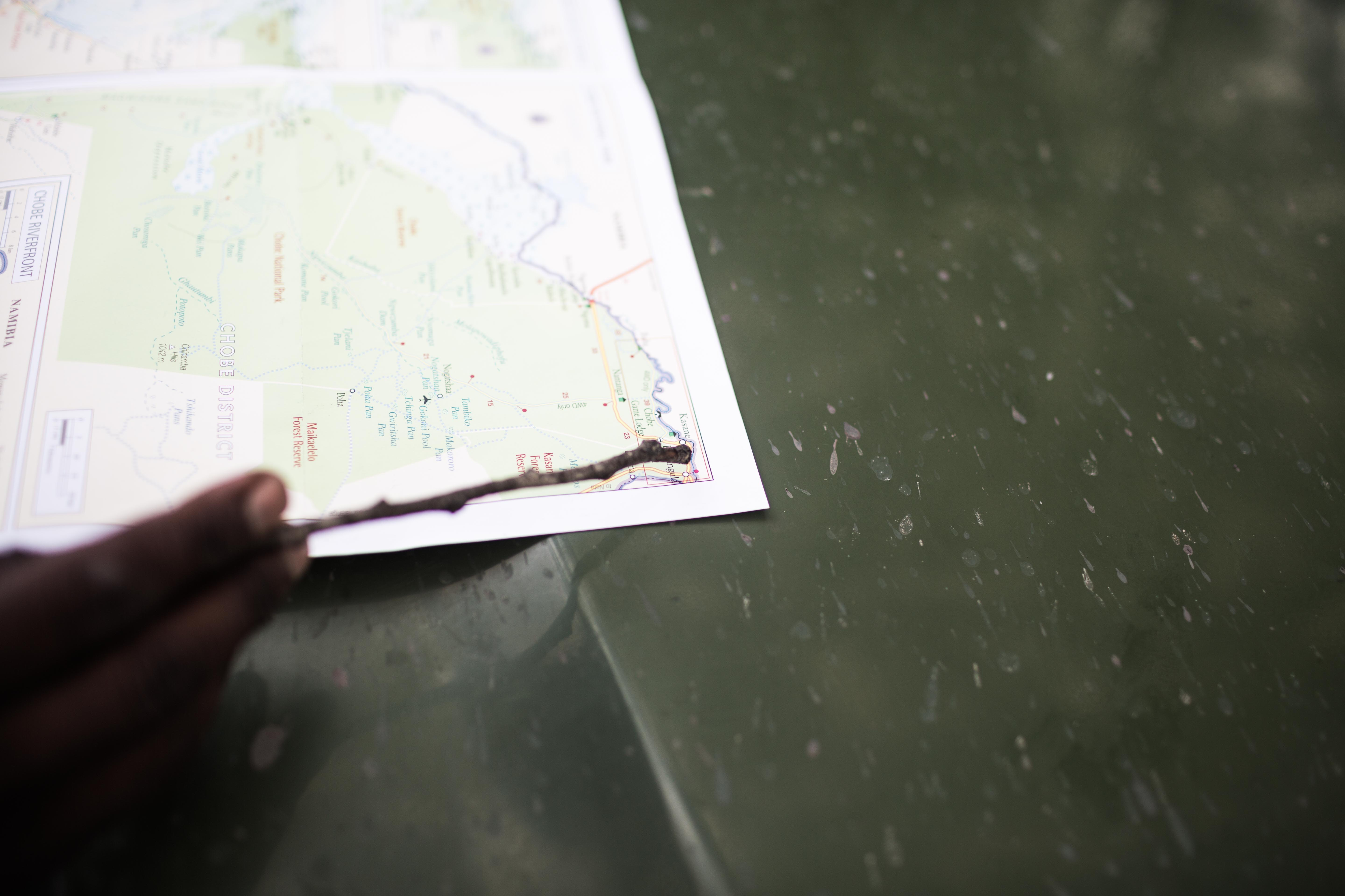 A close-up of a person's hand pointing to a location on a map with a stick