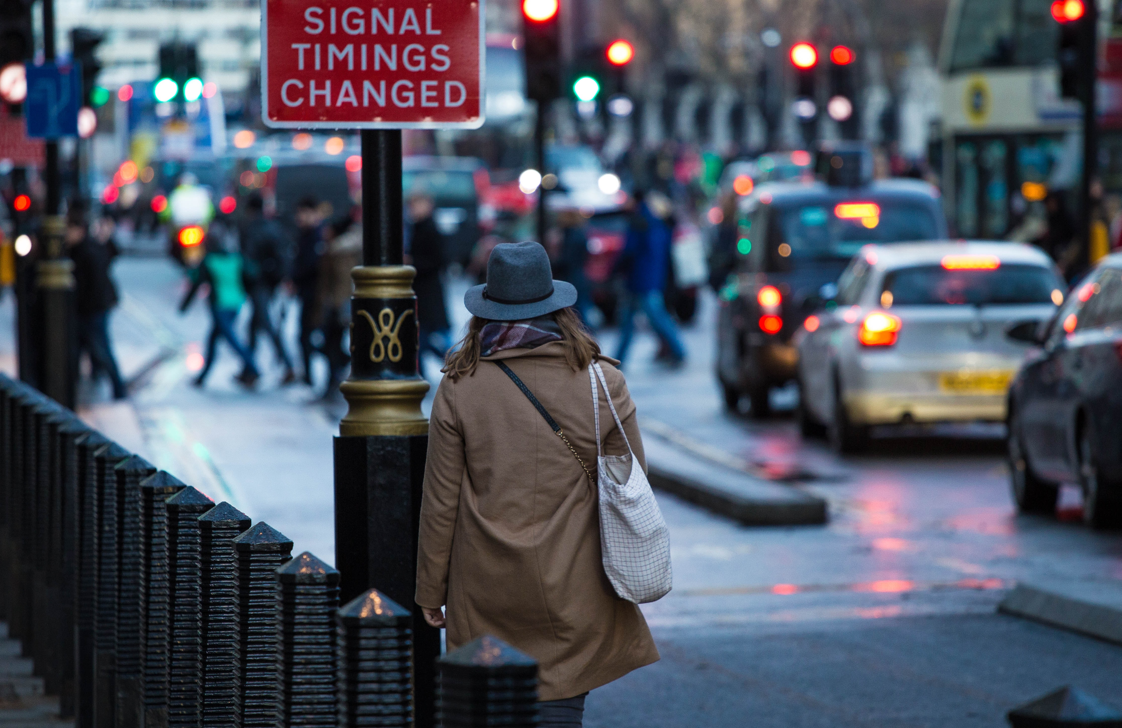 woman walking on sidewalk near red and white signal thing changed road signage
