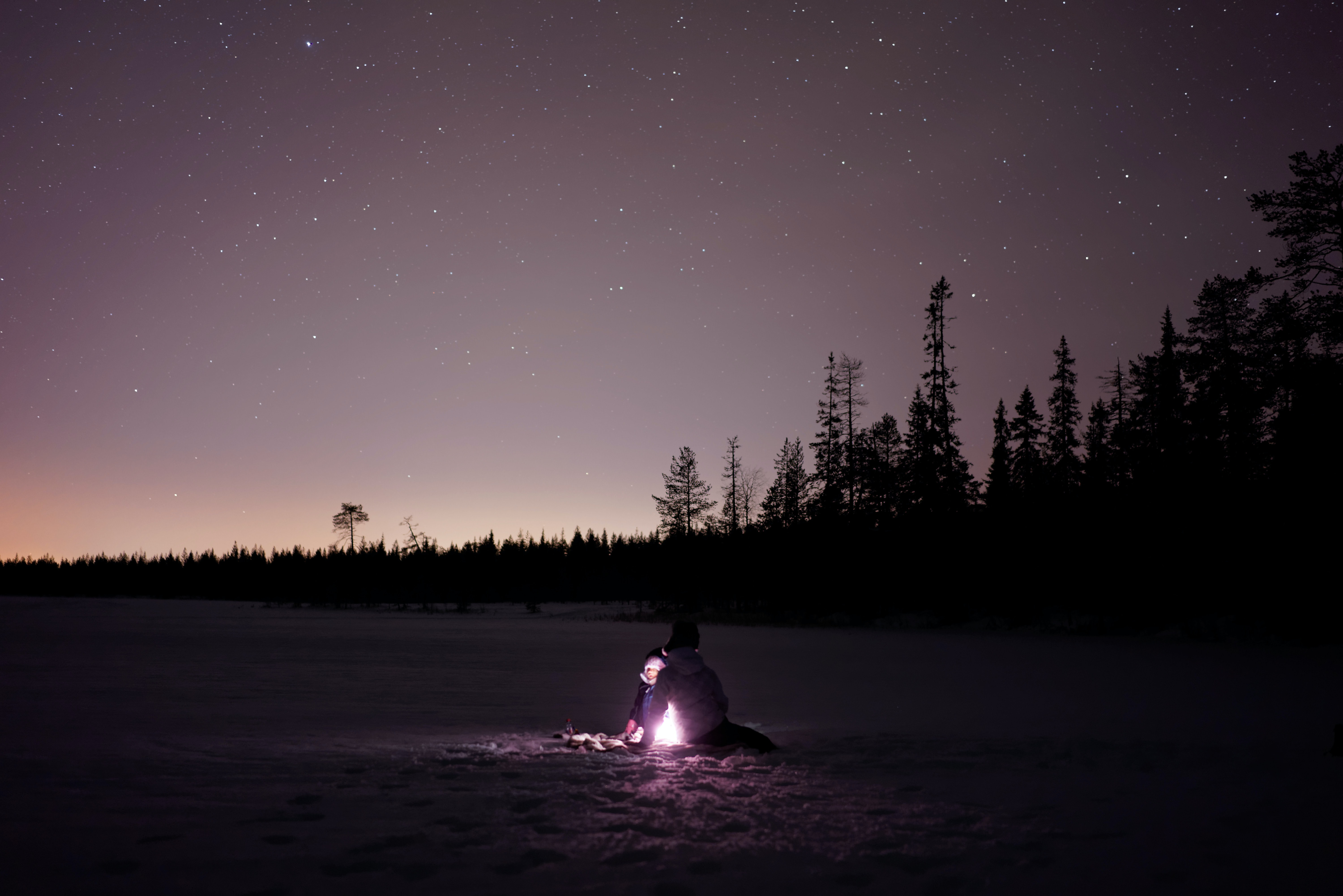 Under a twinkling purple night sky, two children huddle close to a light in the snow