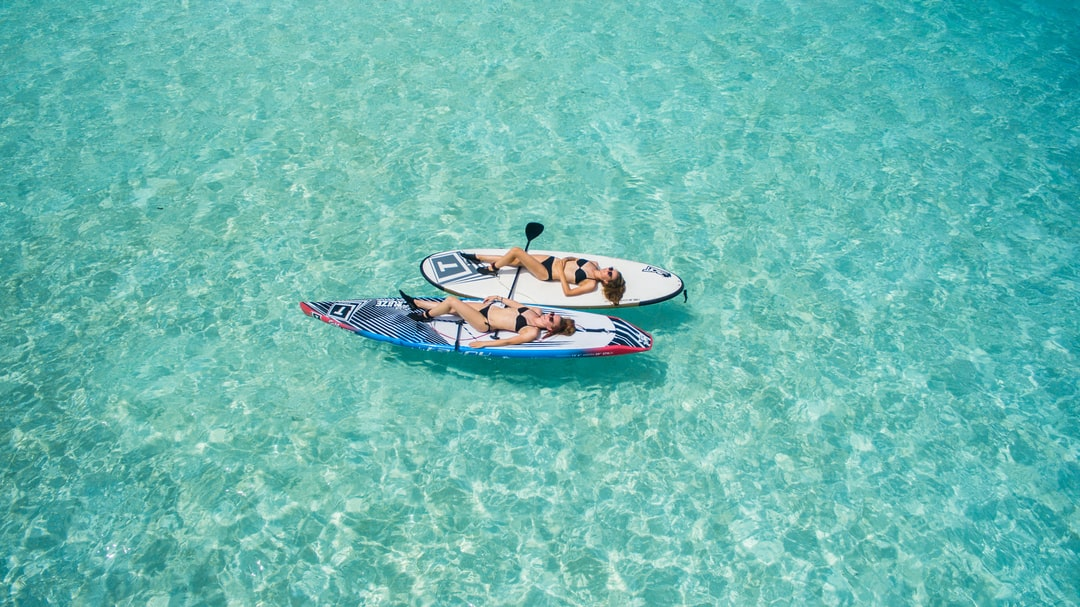 Two young women in bikini sunbathe on wakeboards in the middle of a clear sea