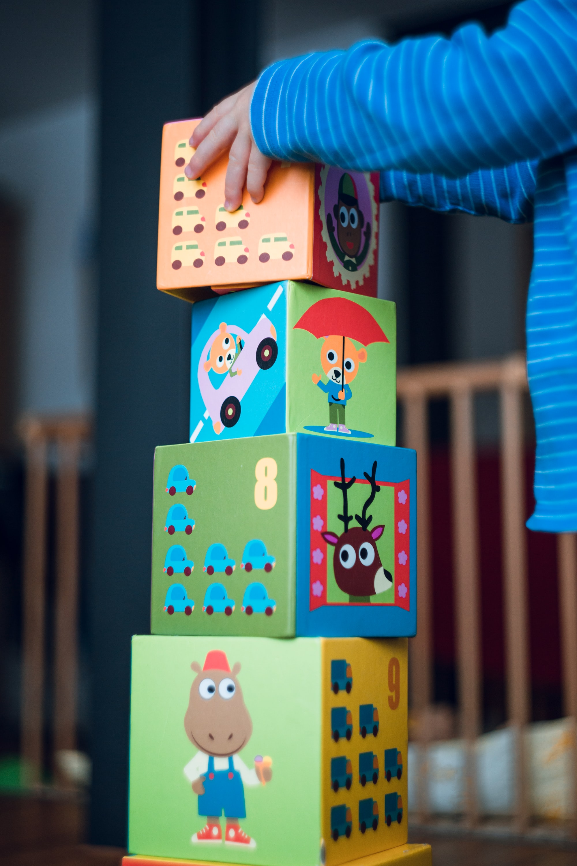 Young boy stacks funny animal comic cardboard boxes. Early childhood motor skills.