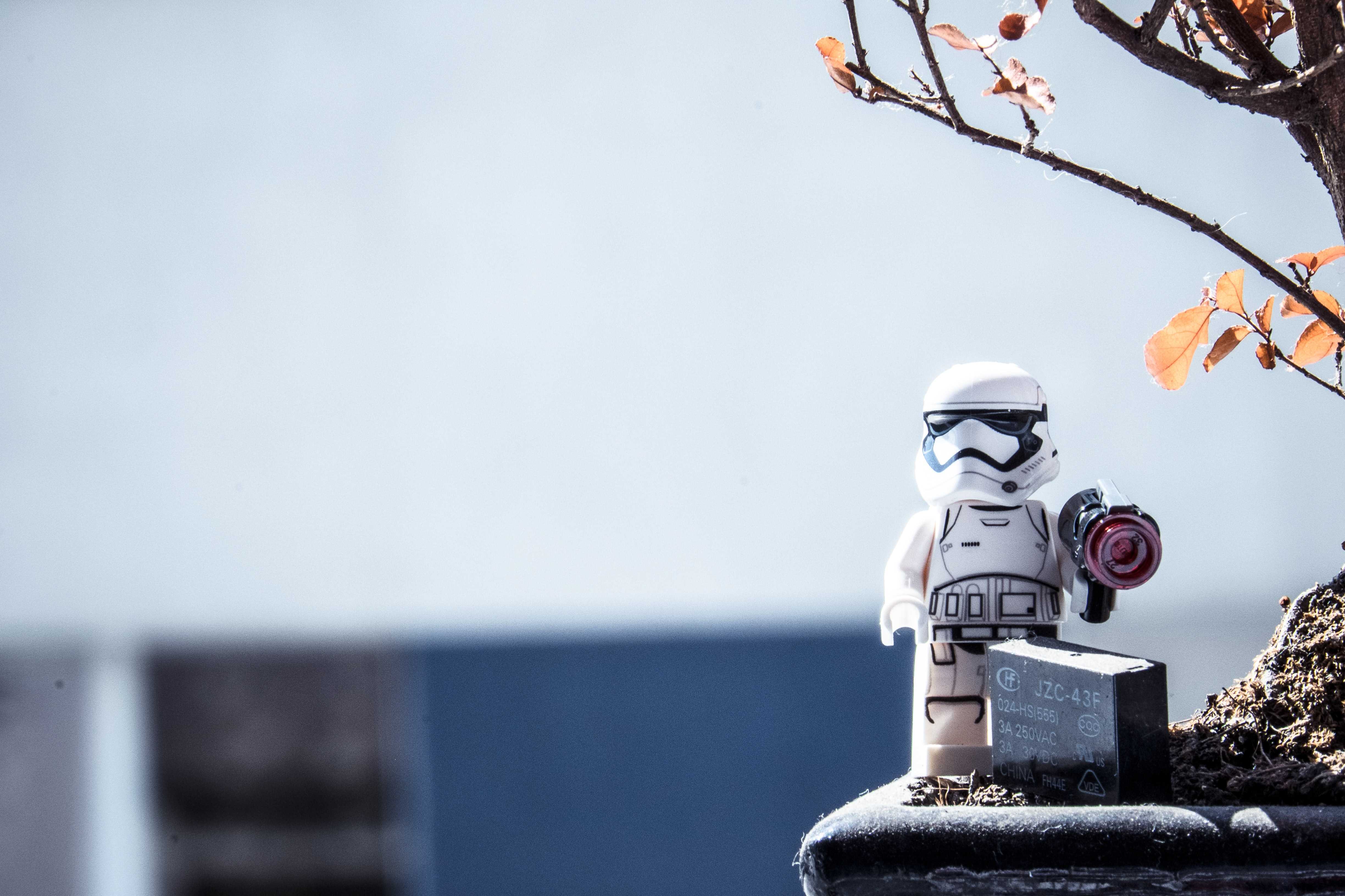 A small figurine of a Star Wars stormtrooper sits on a planter alongside a battery pack