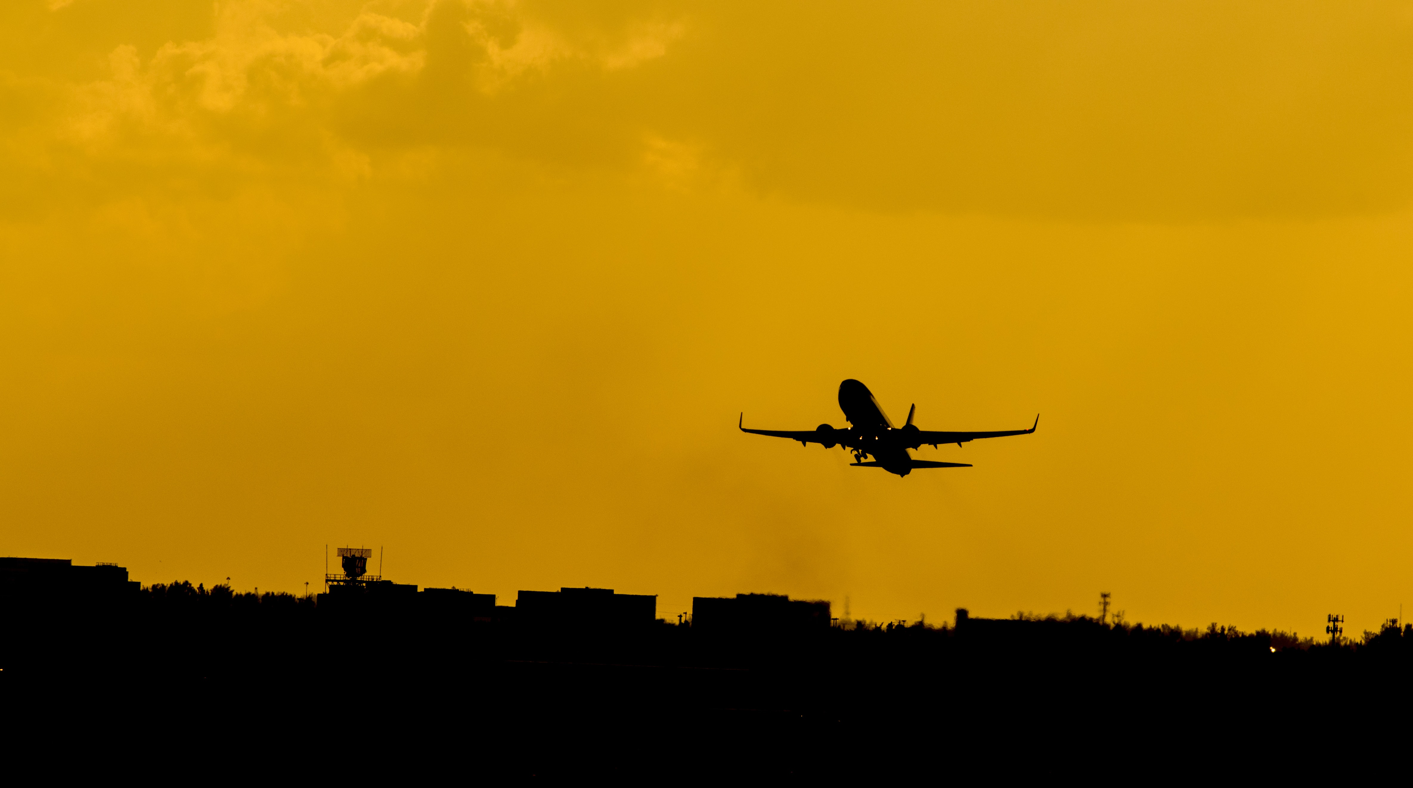 A silhouette of an airplane against an orange sky over an airport