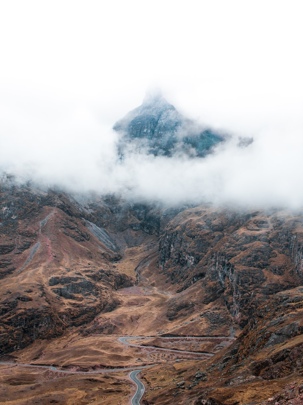 aerial photo of gray road near mountain under white clouds during daytime