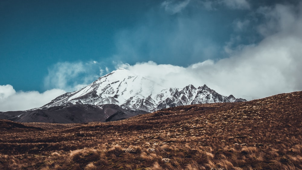 snow-covered mountain under white and blue sky