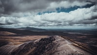 aerial photography of brown mountains with cloudy skies