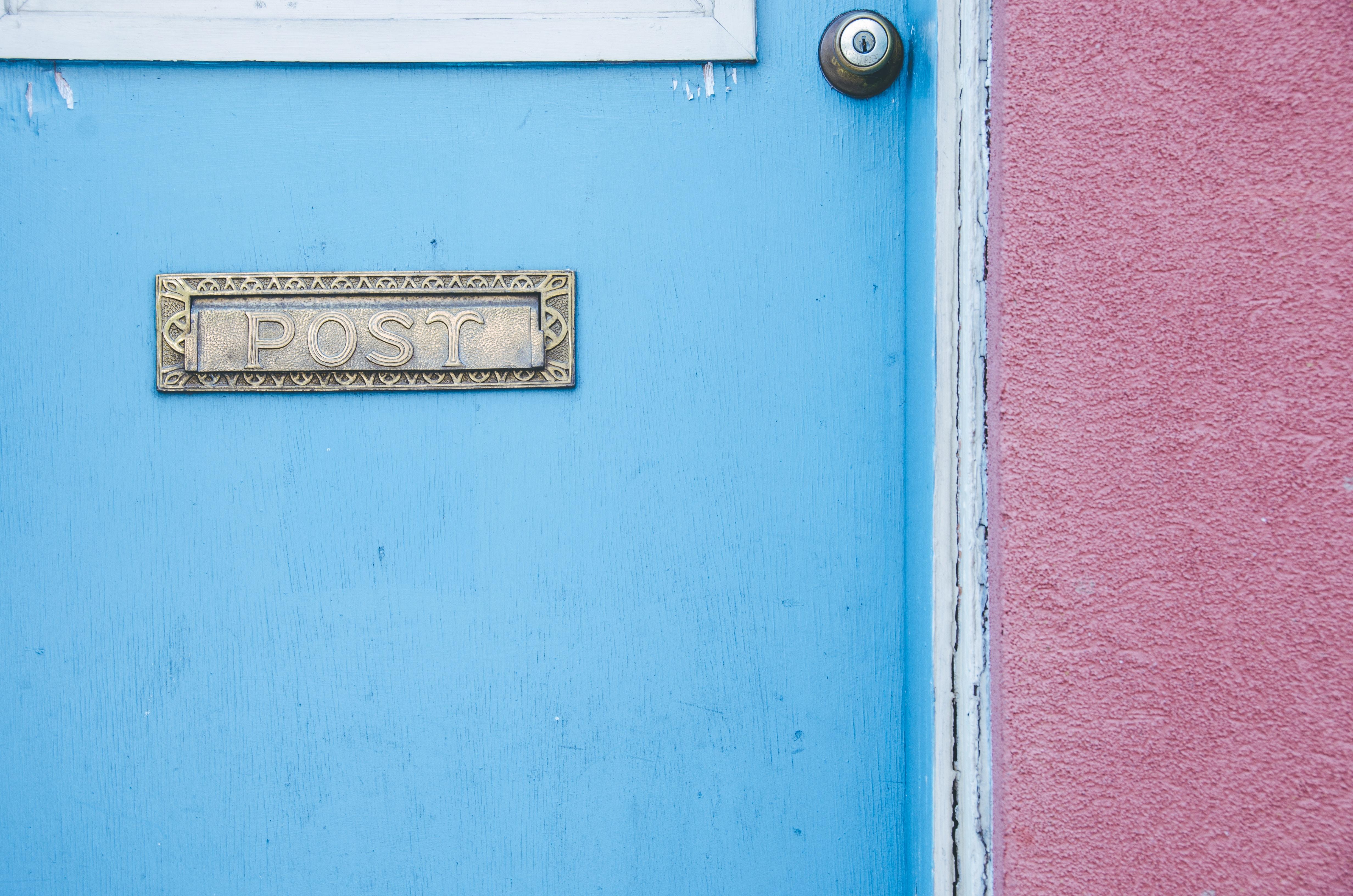 gray post signage on blue wooden door